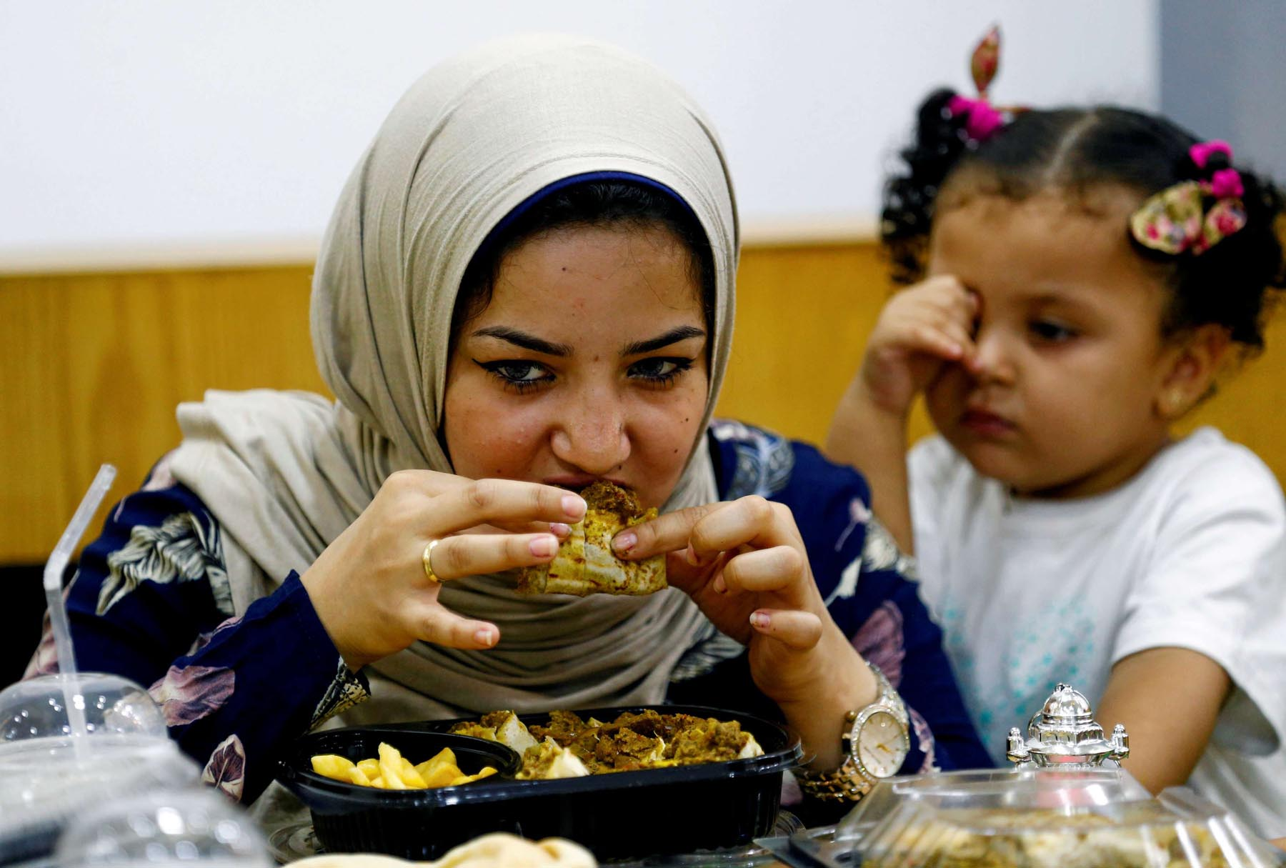 Unhealthy habits. A woman eats at a fast food restaurant in Damanhour.