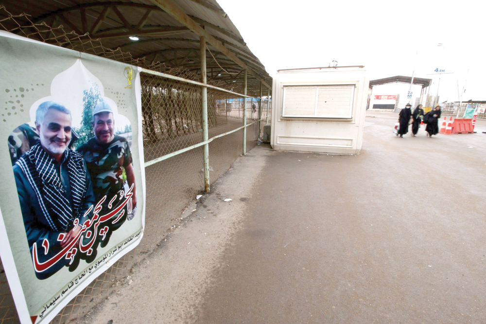 A poster of a member of Shia Popular Mobilisation Forces with Iranian Revolutionary Guard Corps Commander Qassem Soleimani is seen at the Iraqi side of the Shalamcha Border Crossing. (Reuters)