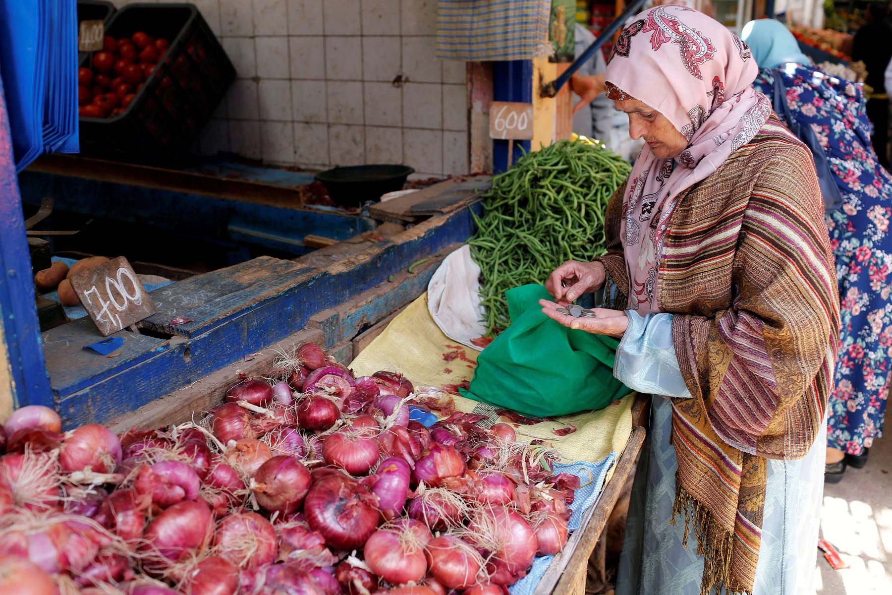 A Moroccan woman counts change at a vegetable market in Casablanca.          (Reuters)