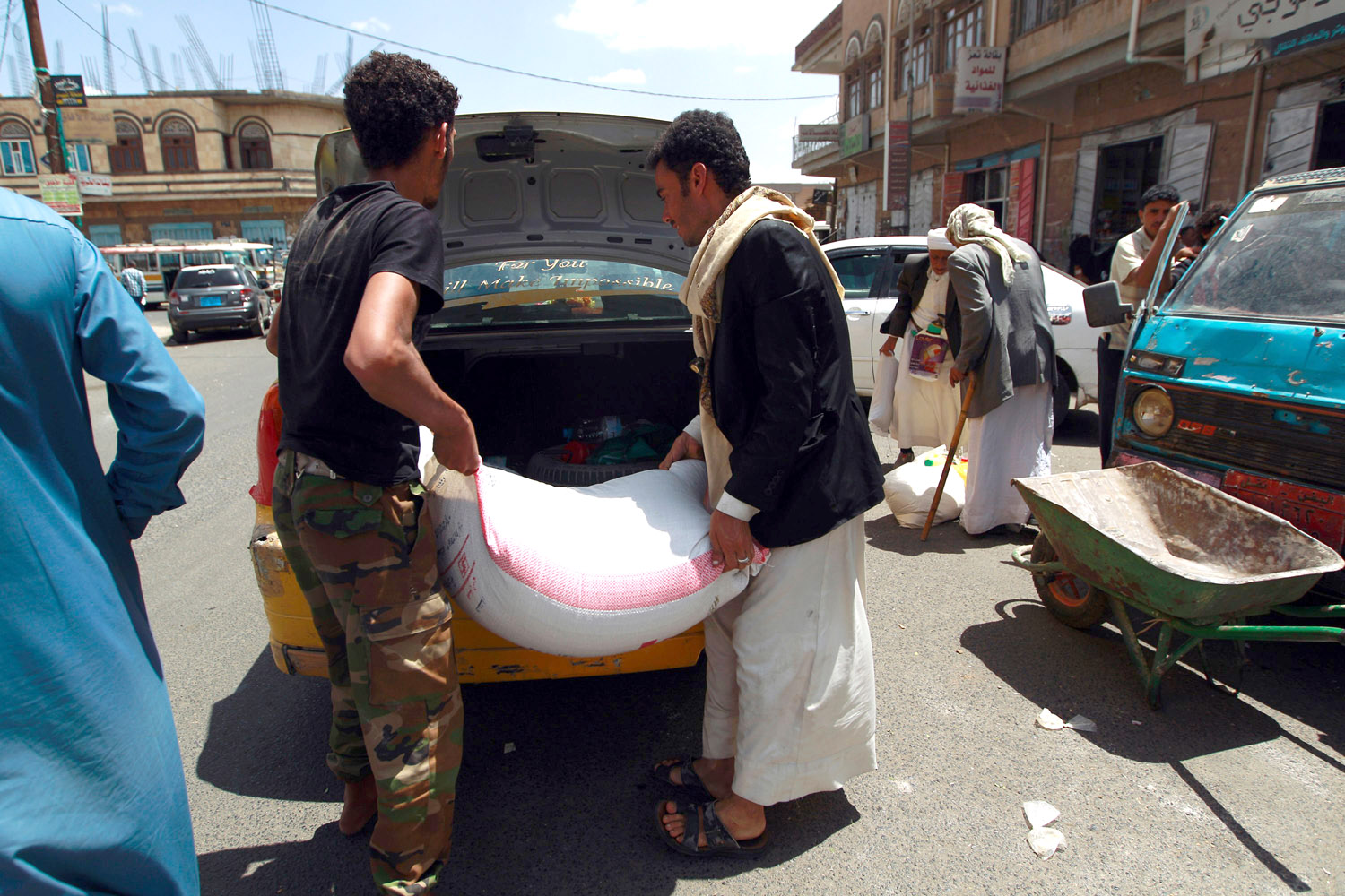 Yemeni men carry food aid provided by the World Food Programme in Sana'a. (sAFP)