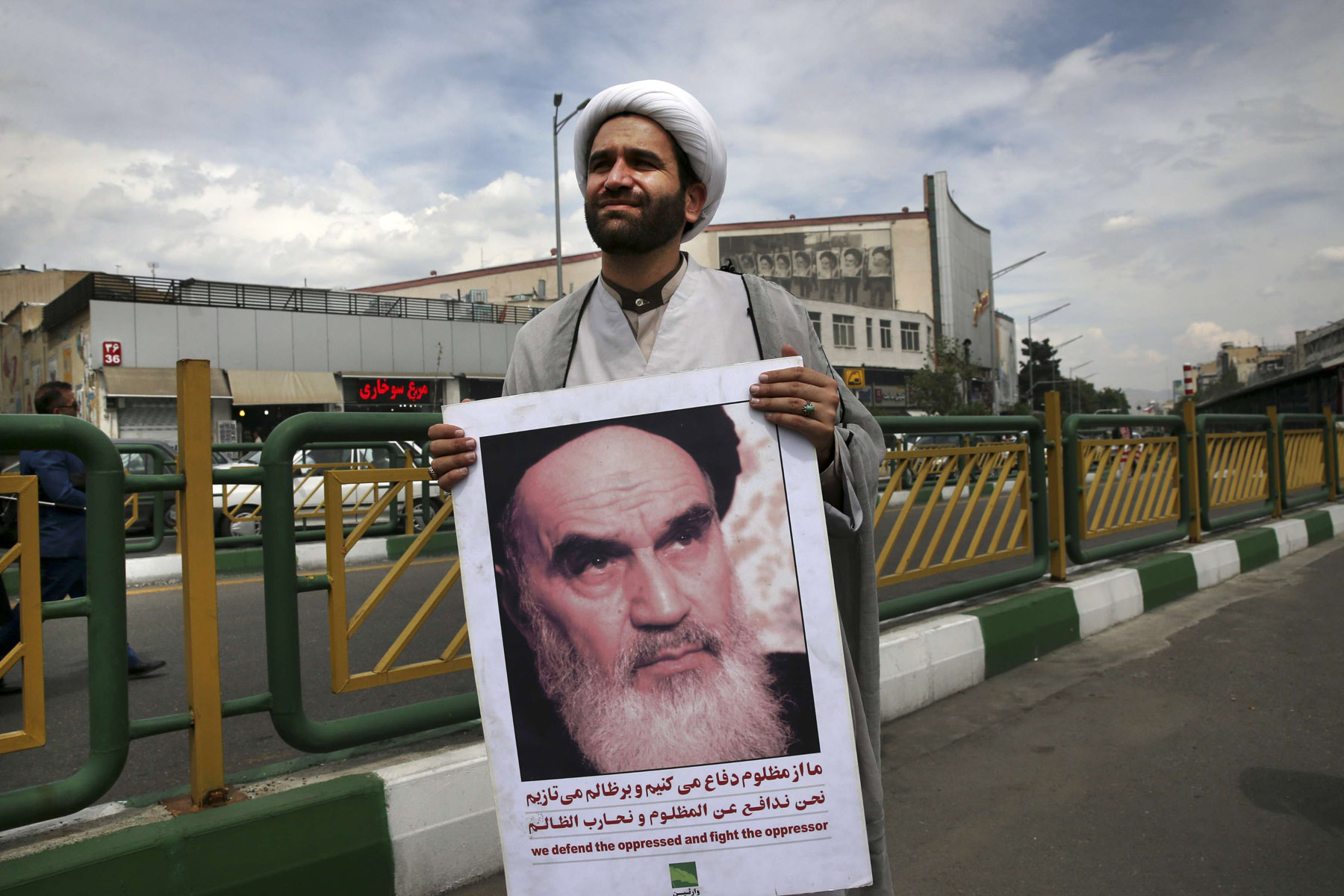 Hanging by a thread. A cleric holds a poster showing a portrait of the late founder of the Islamic Republic Ayatollah Ruhollah Khomeini in Tehran.  (AP)