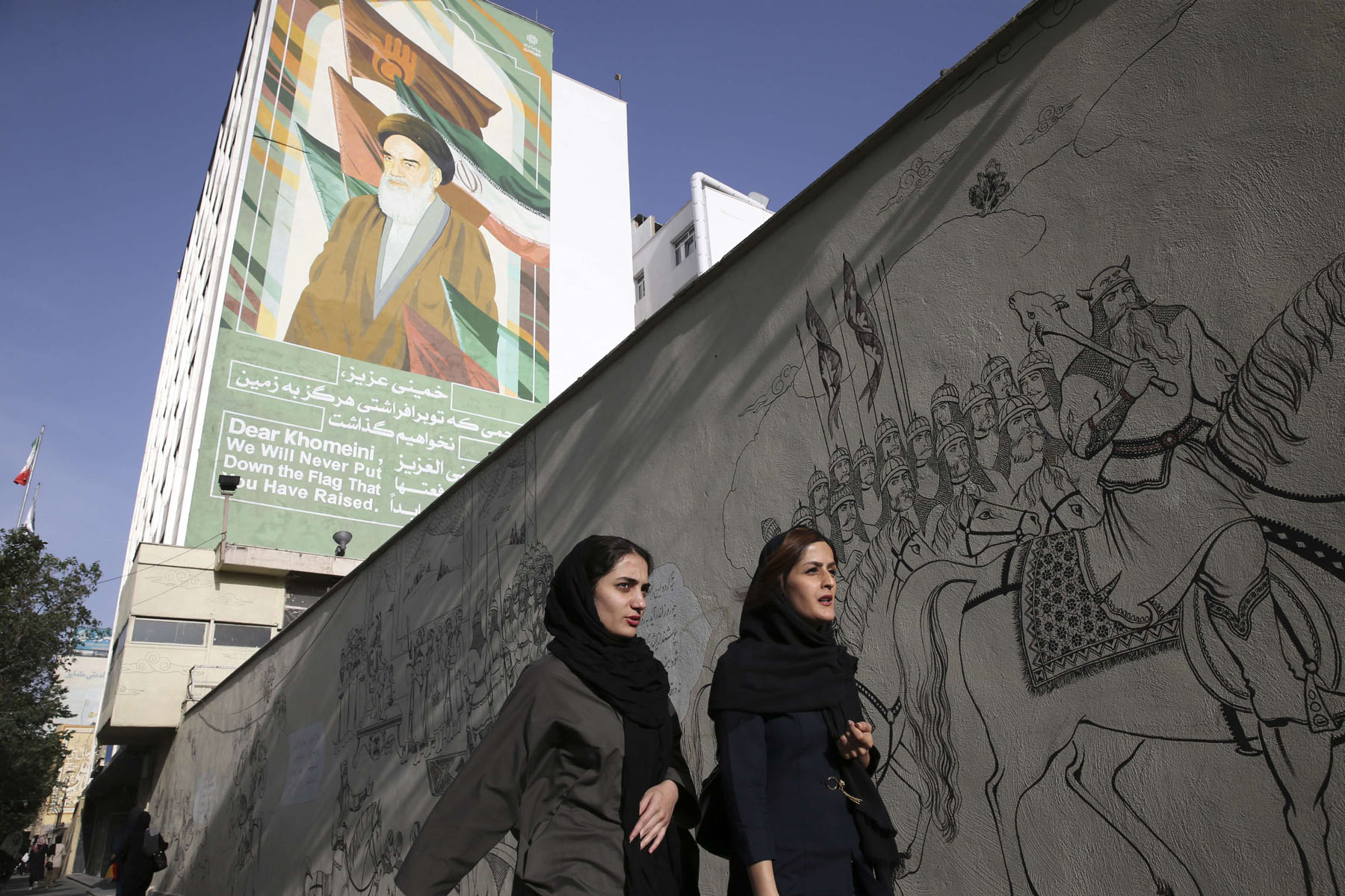 Iranian women walk past a portrait of the late founder of the Islamic Republic Ayatollah Khomeini in Tehran. (AP)