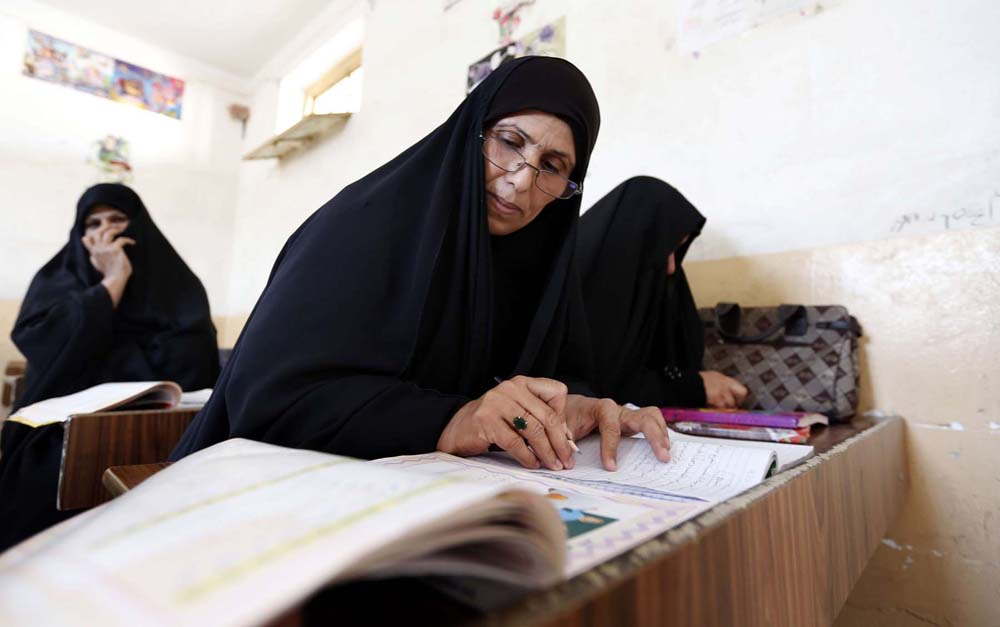 Catching up. Iraqi women take part in an Iraqi government's literacy programme for adults in Najaf. 			         (AFP)