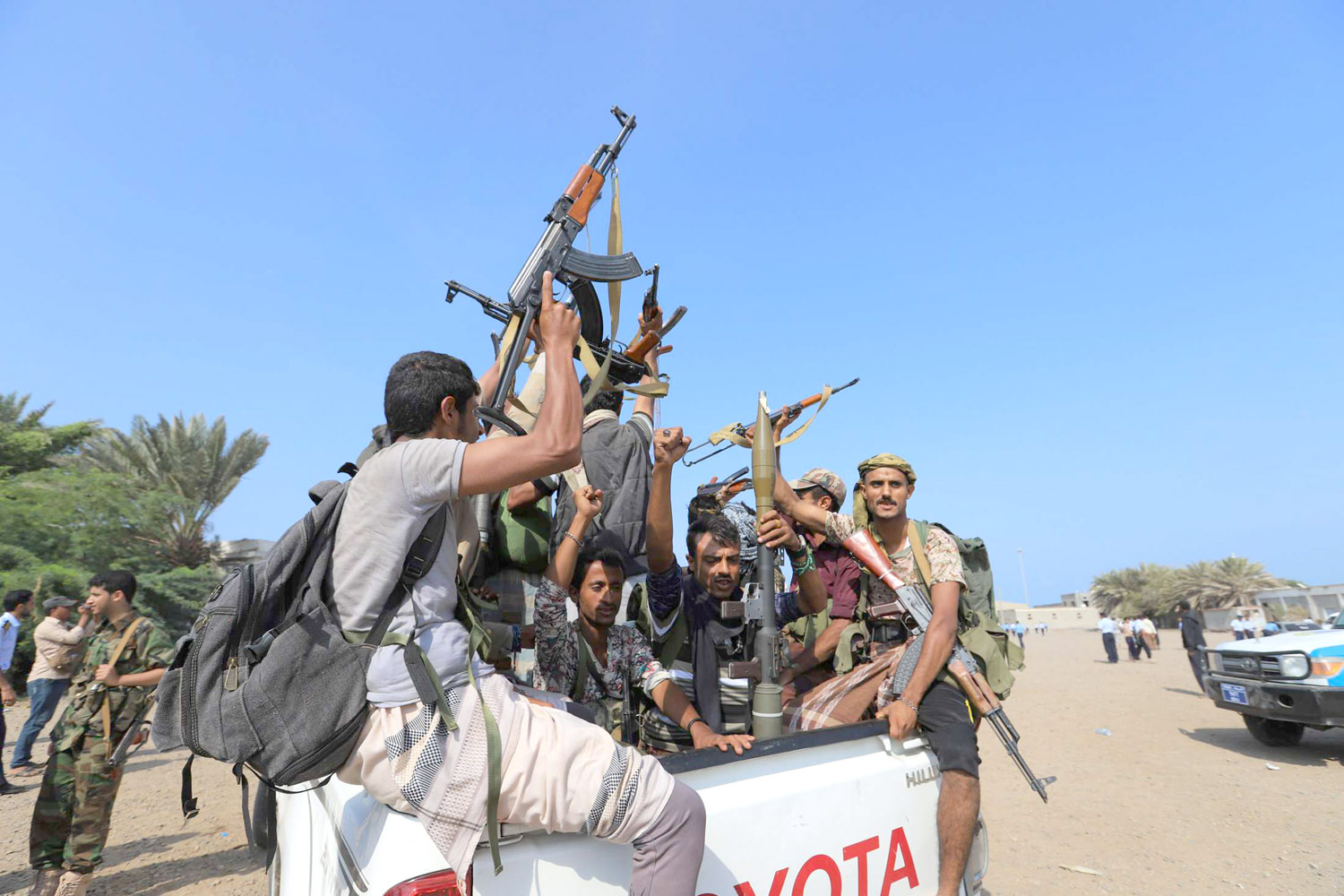 Houthi fighters ride on the back of a truck as they withdraw from the Red Sea city of Hodeidah, December 29. (Reuters)