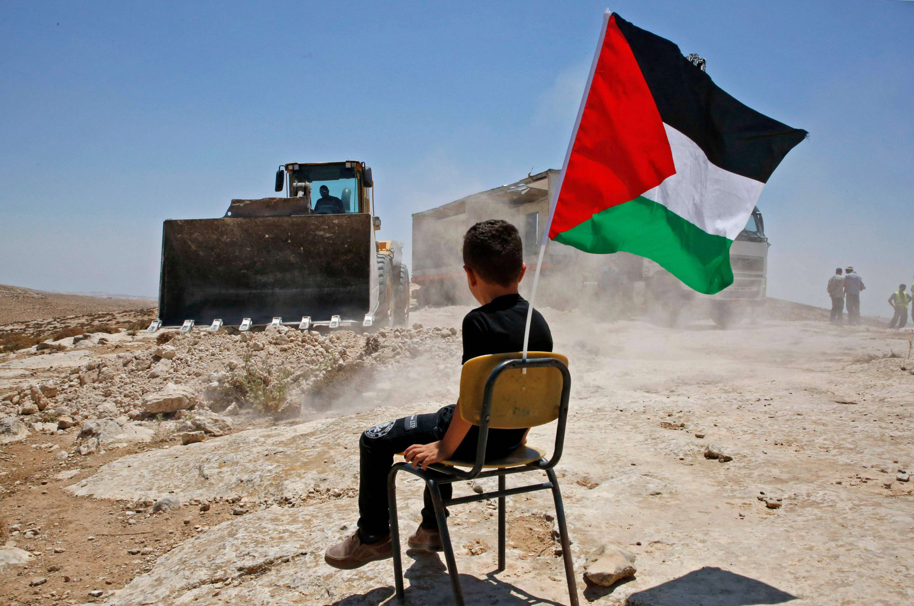 A Palestinian boy sits on a chair as Israeli bulldozers demolish a school site in the village of Yatta, south of Hebron, last July. (AFP)