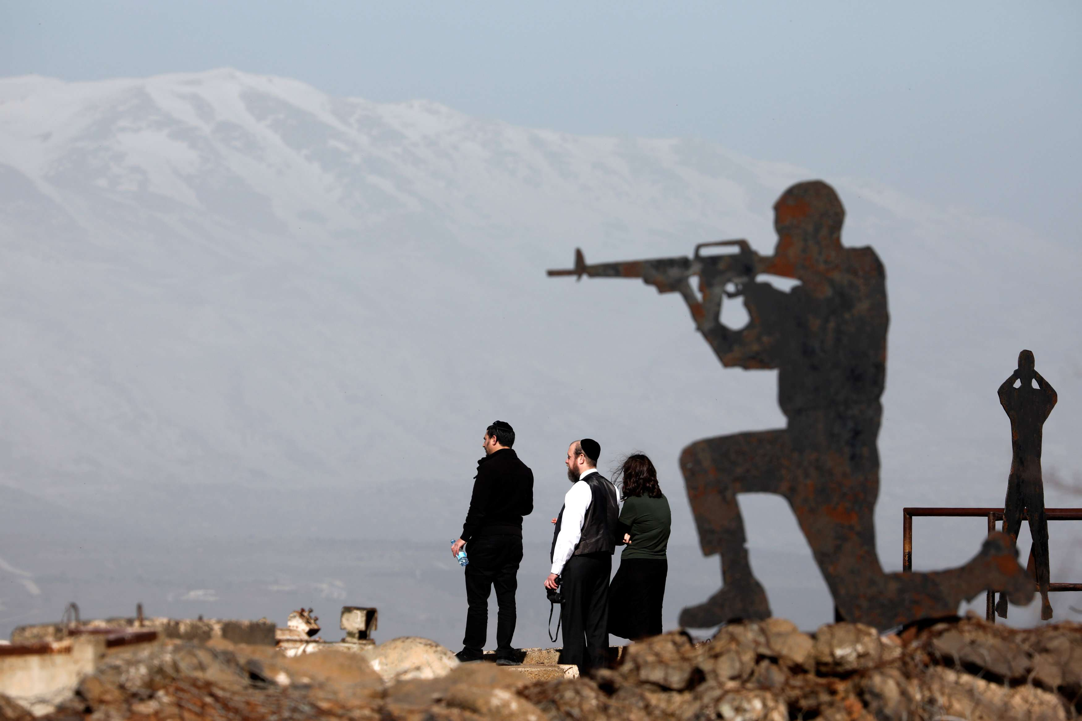 People stand next to metal sculptures at Mount Bental, an observation post in the Israeli-occupied Golan Heights. (Reuters)