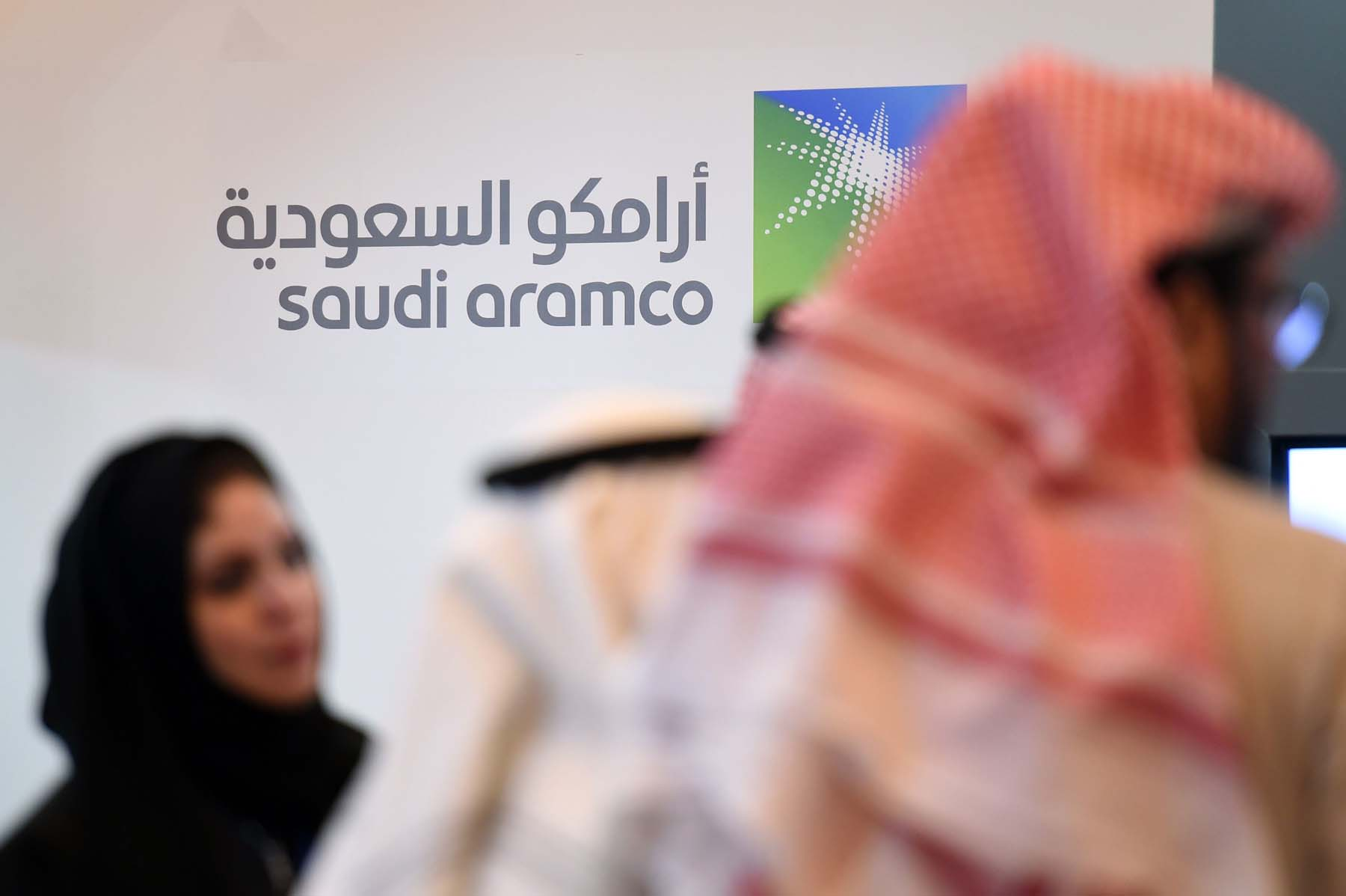 Saudi and foreign investors stand in front of the logo of Aramco in Riyadh. (AFP)