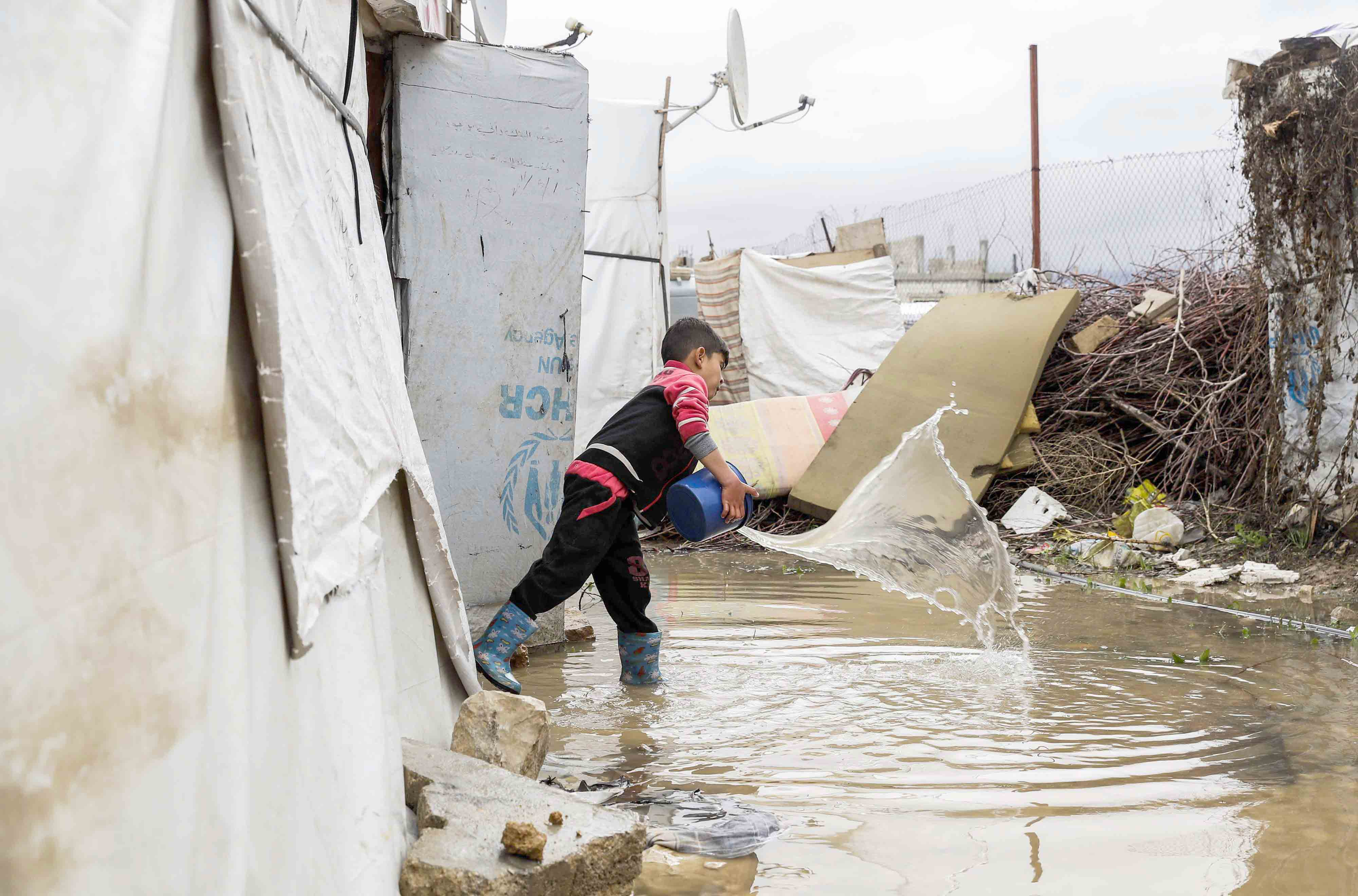 A Syrian child uses a bucket to bale out water from his tent in Lebanon's Bekaa Valley. (AFP)