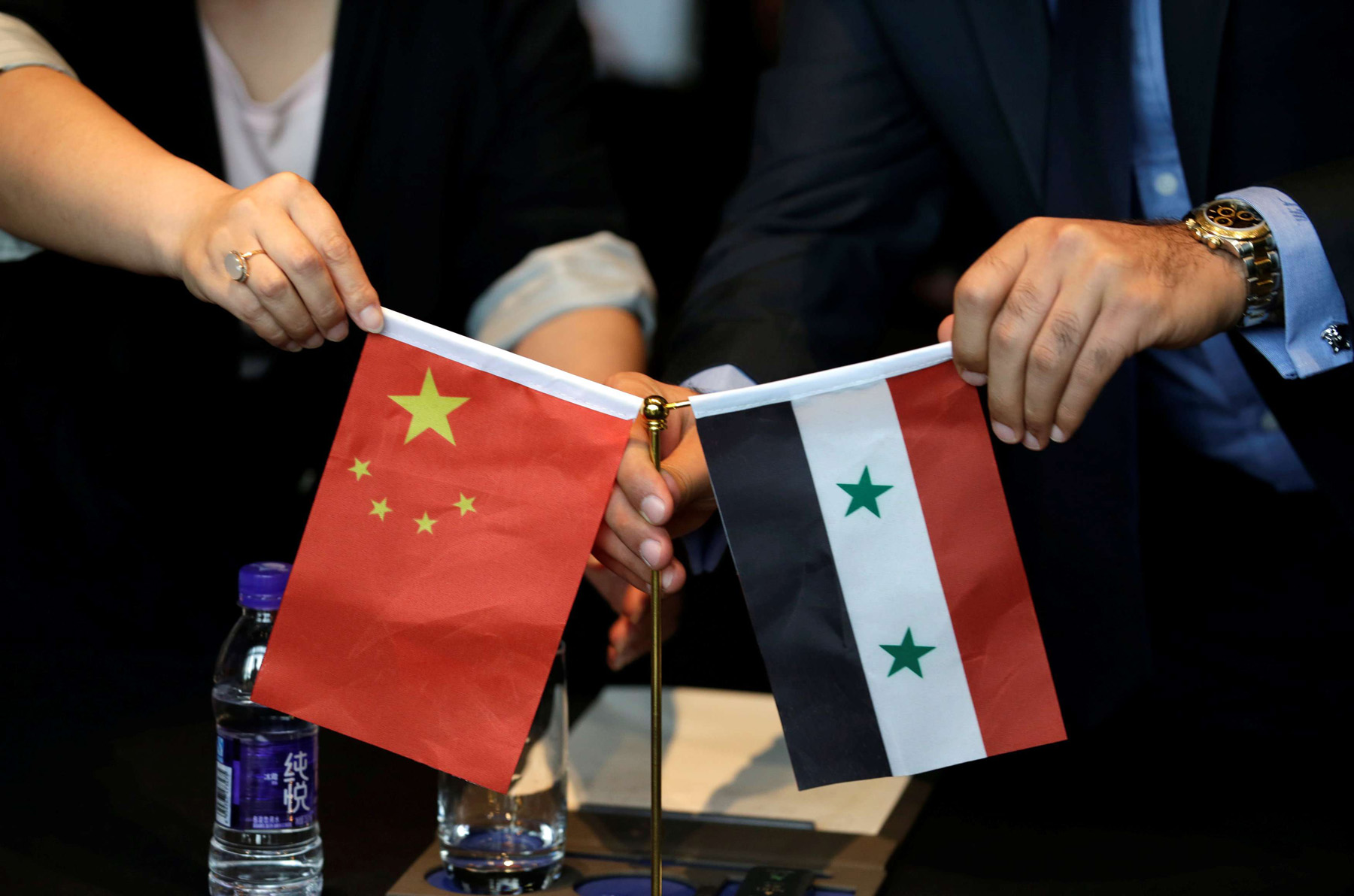 Chinese and Syrian businessmen set up their national flags during a meeting to discuss reconstruction projects in Syria. (Reuters)