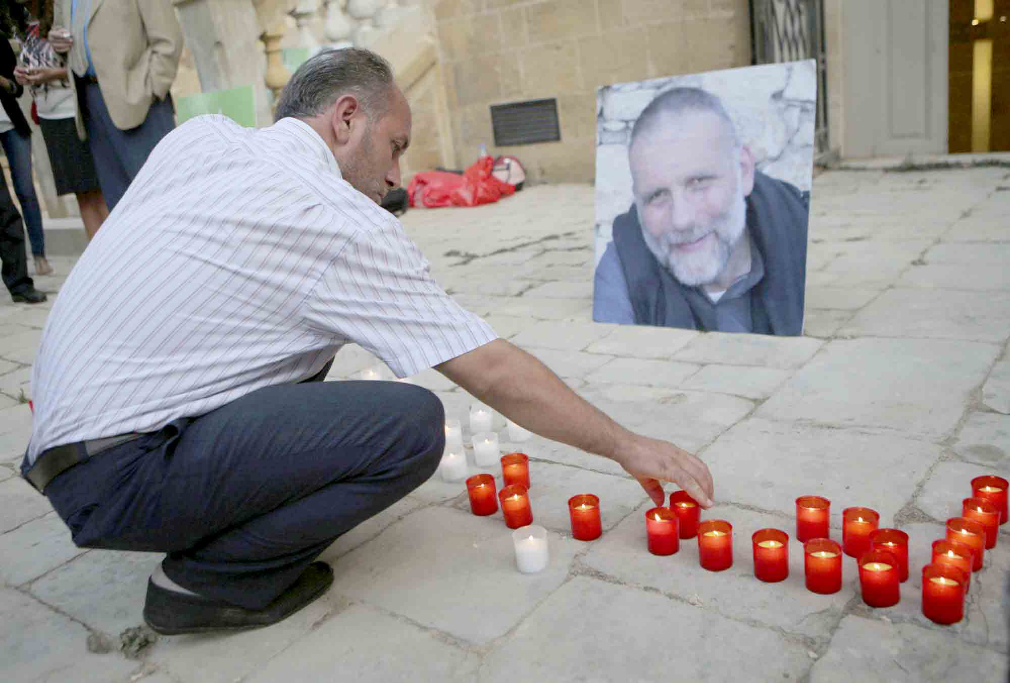 A glimmer of hope. A Syrian man lights a candle in front of a portrait of Italian Jesuit priest Father Paolo Dall'Oglio during a vigil calling for his release at the St. Joseph Church in Beirut.  (AP)