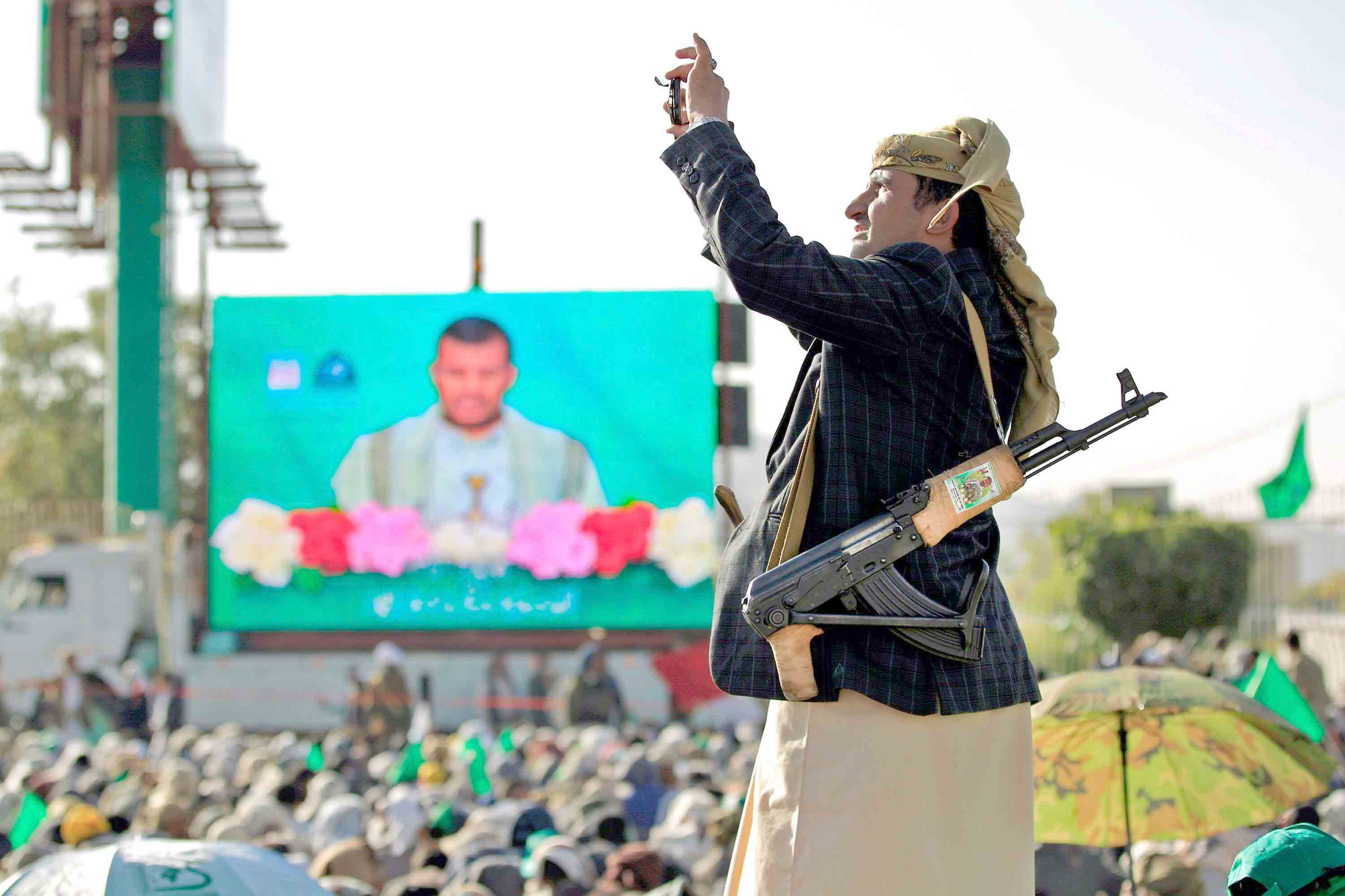 Ideological indoctrination. A Houthi rebel films with his cell phone as his comrades and their supporters watch on a big screen a speech given by leader Abdul-Malik al-Houthi during a rally in Sana'a. (AFP)