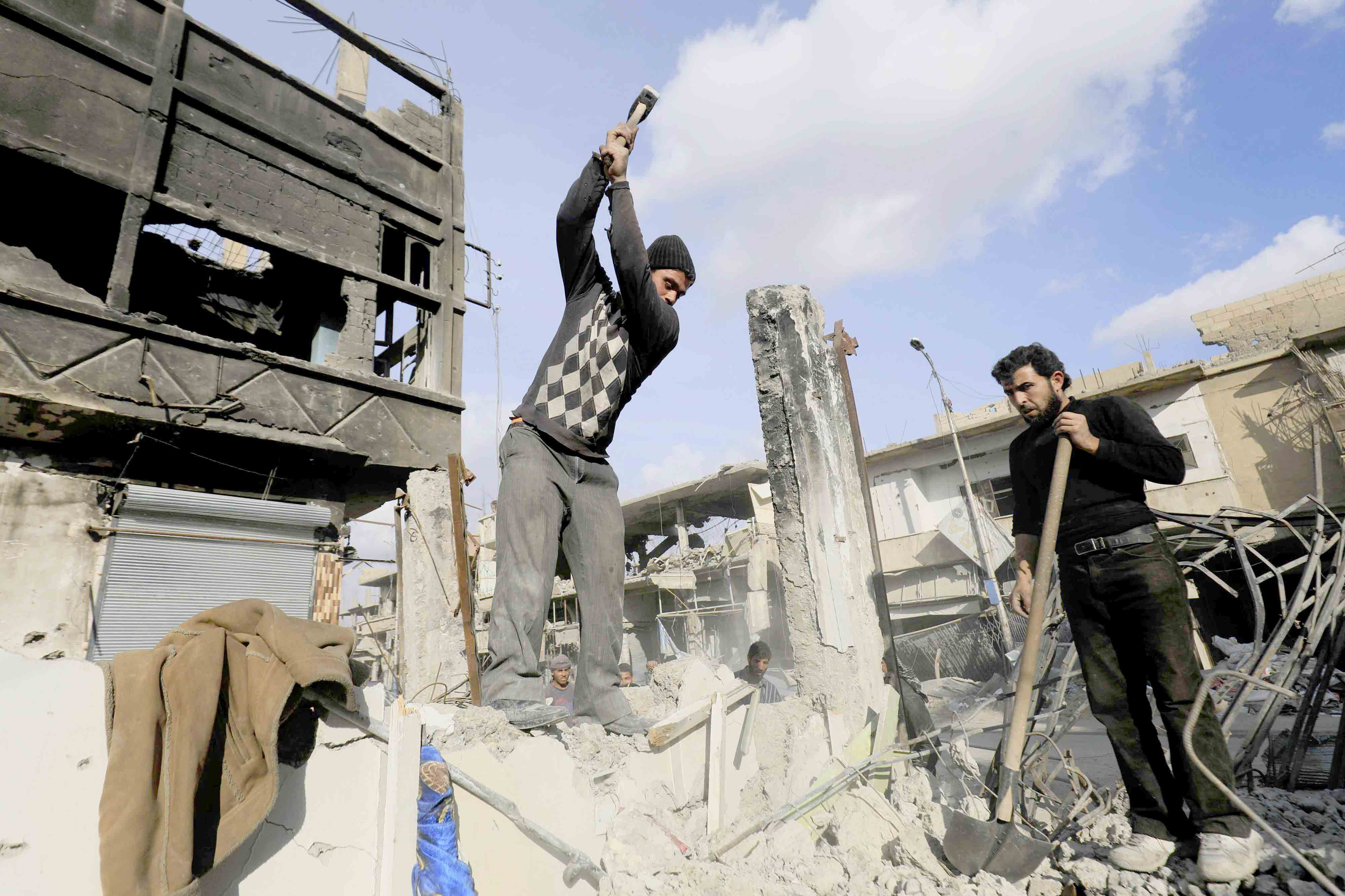 Syrian men work on reconstructing a damaged building in Raqqa. (AFP)