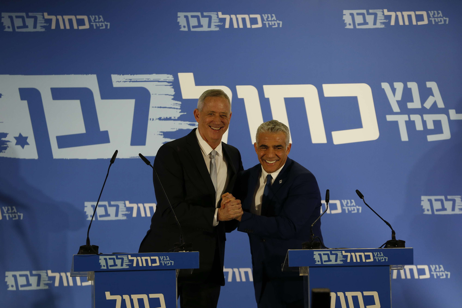 Retired Israeli military chief Benny Gantz (L) smiles with Yair Lapid,  head of the Yesh Atid party, as they launch a joint list for the upcoming Israeli elections in Tel Aviv, February 21. (AP)
