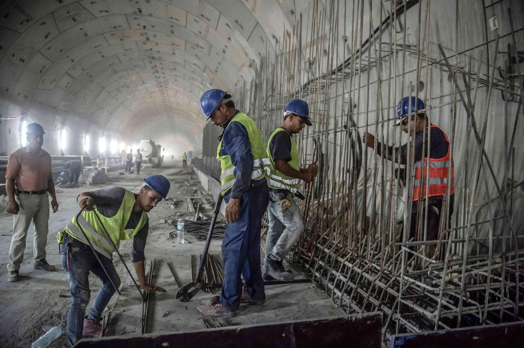 Labourers set up and fix a steel mesh at the site of a new twin-tube road tunnel under construction along the Suez Canal in Ismailia.        (AFP)