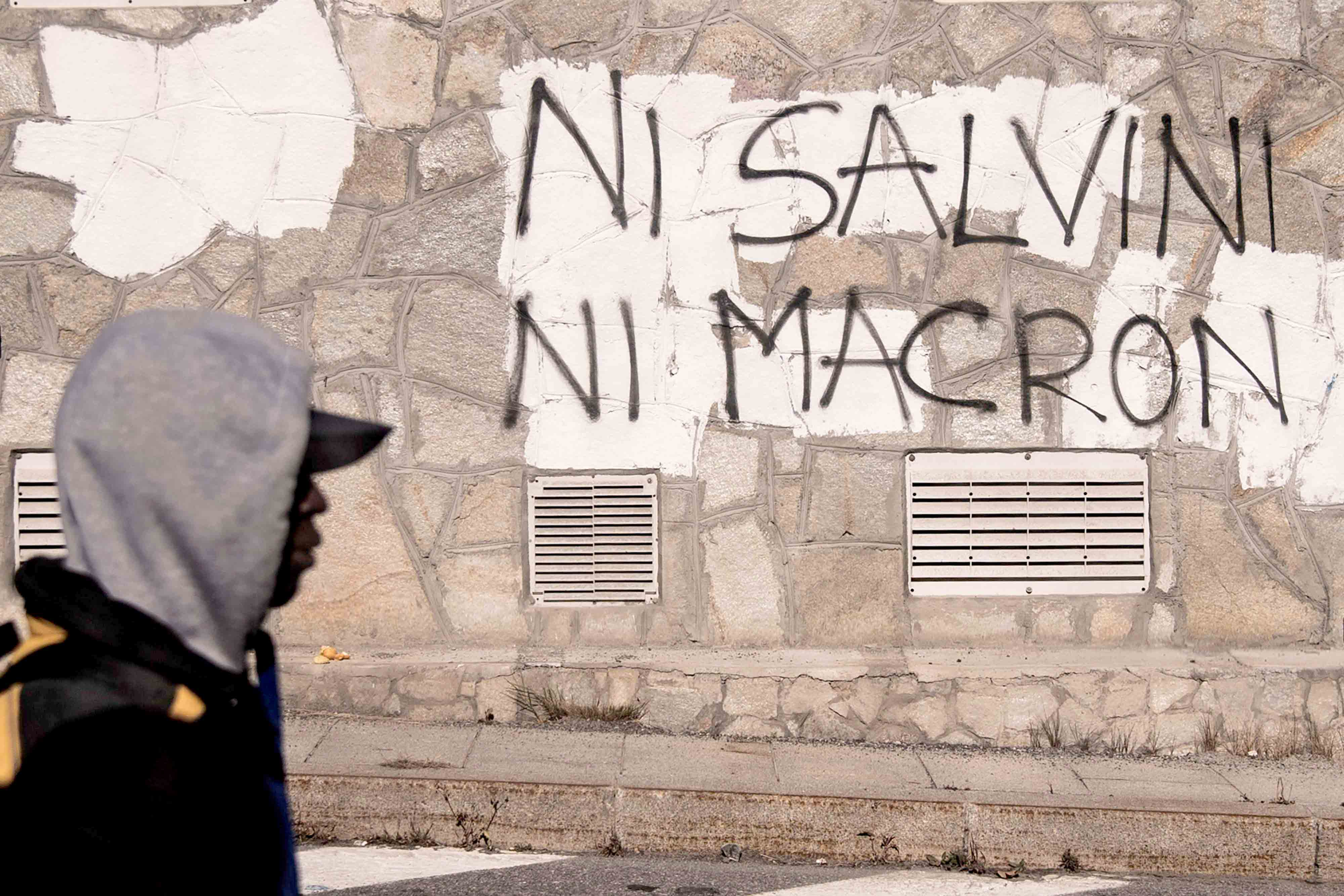 "A migrant walks past an inscription reading, in French, ""Neither Salvini, nor Macron"" in the Alpine border town of Claviere, some 100km west of Turin. (AFP)"