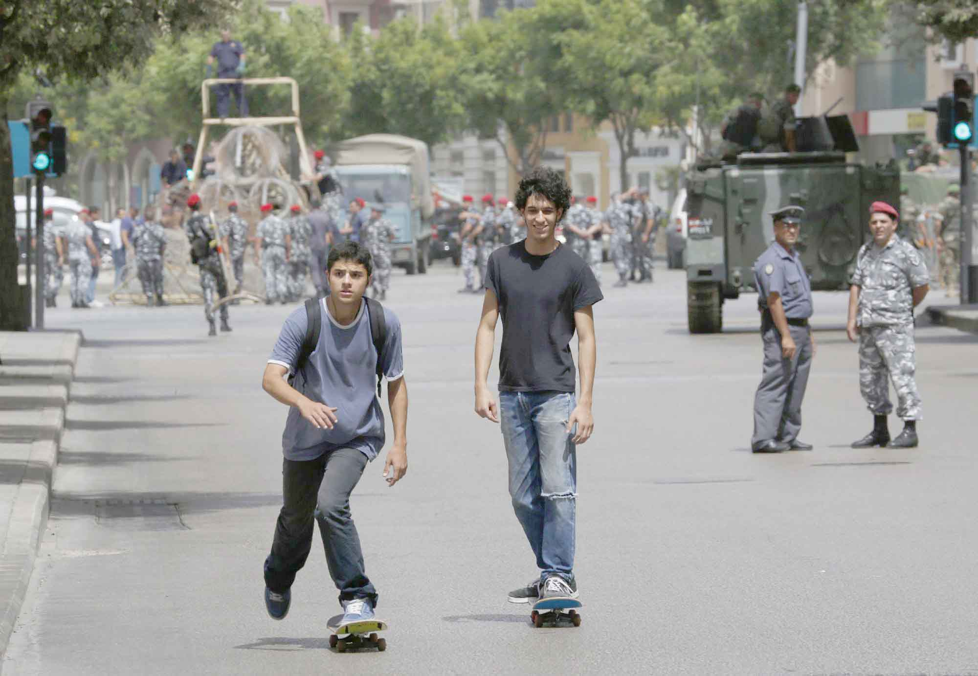 Young Lebanese men on skateboards pass by a police officer and a soldier securing a street they have closed off in Beirut. (Reuters)