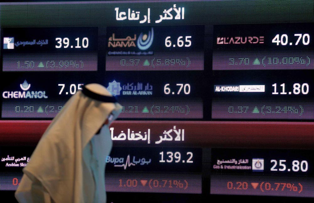 An investor walks past a screen displaying stock information at the Saudi Stock Exchange (Tadawul)  in Riyadh,  June 29, 2016.                   (Reuters)