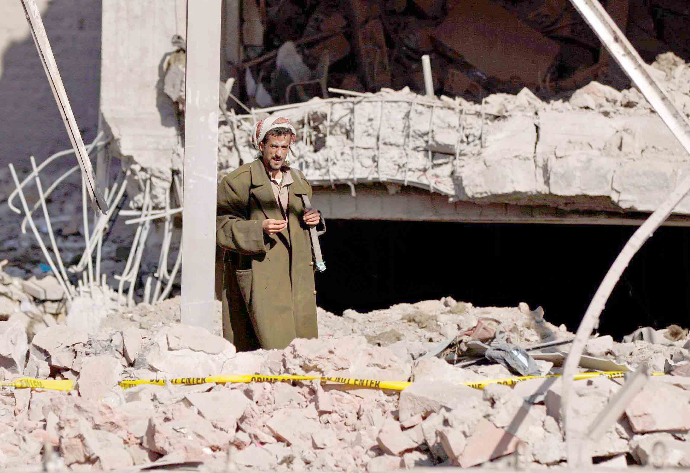 A Houthi fighter stands in the rubble of a building in Sana'a. (AFP)
