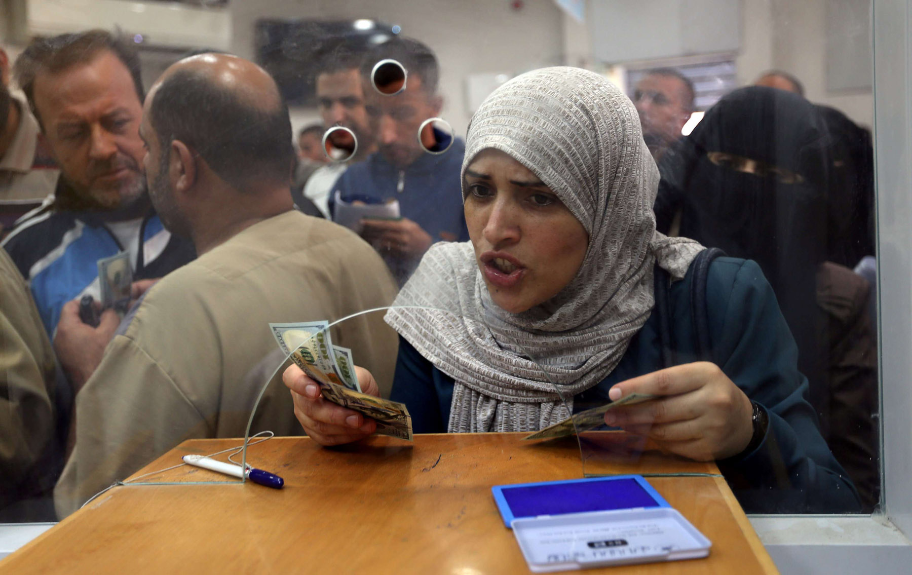 Tough days. A Palestinian employee receives her salary in southern Gaza, last November. (Reuters)