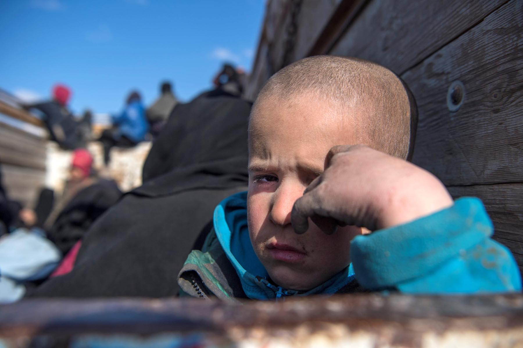 A boy looks on as civilians fleeing the battered Islamic State-held holdout of Baghouz in eastern Syria sit in the back of a truck, February 11.                                                                                    (AFP)