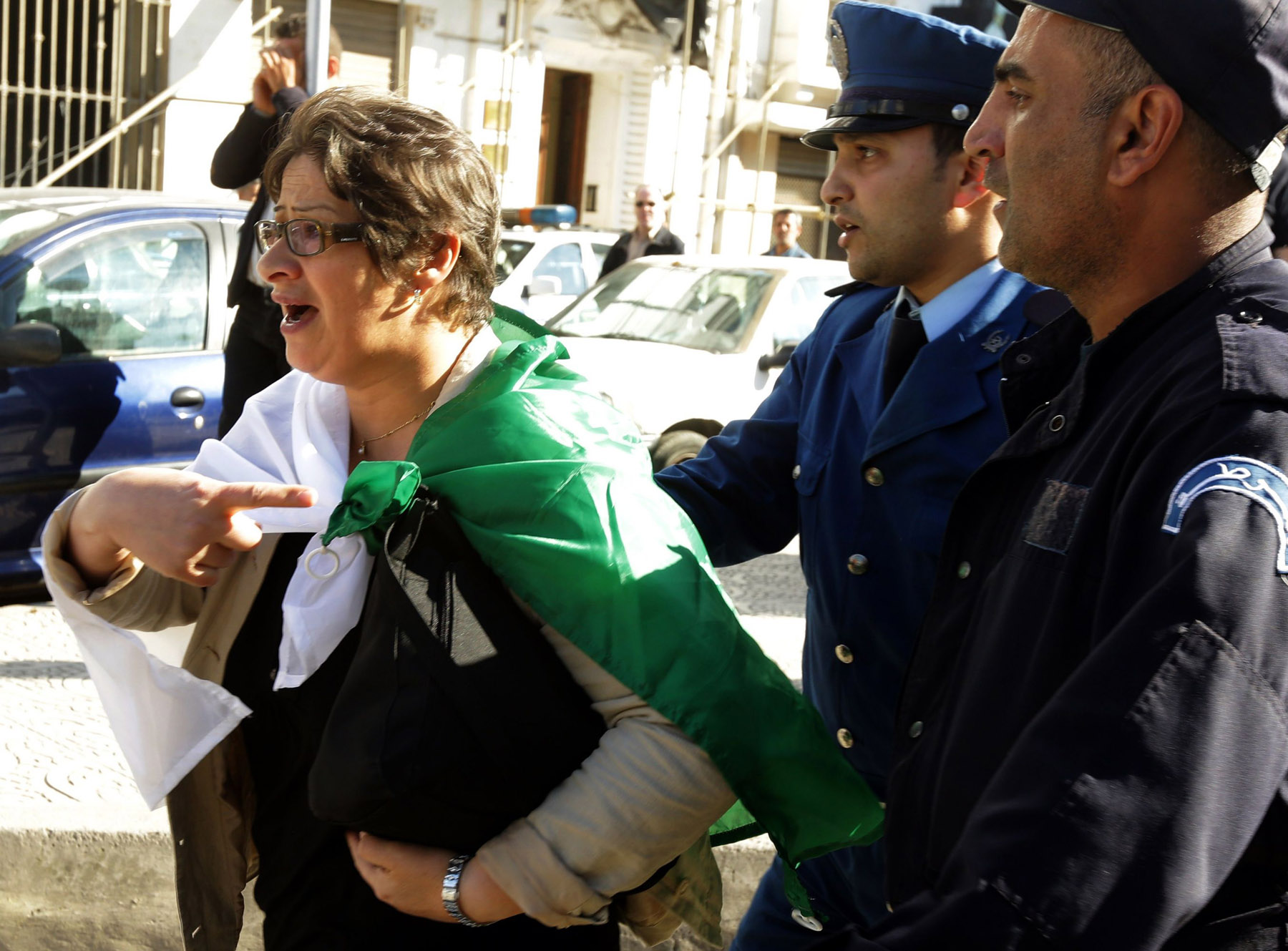 A supporter of the Algerian opposition gestures as she is pushed away by police officers in Algiers. (AFP)