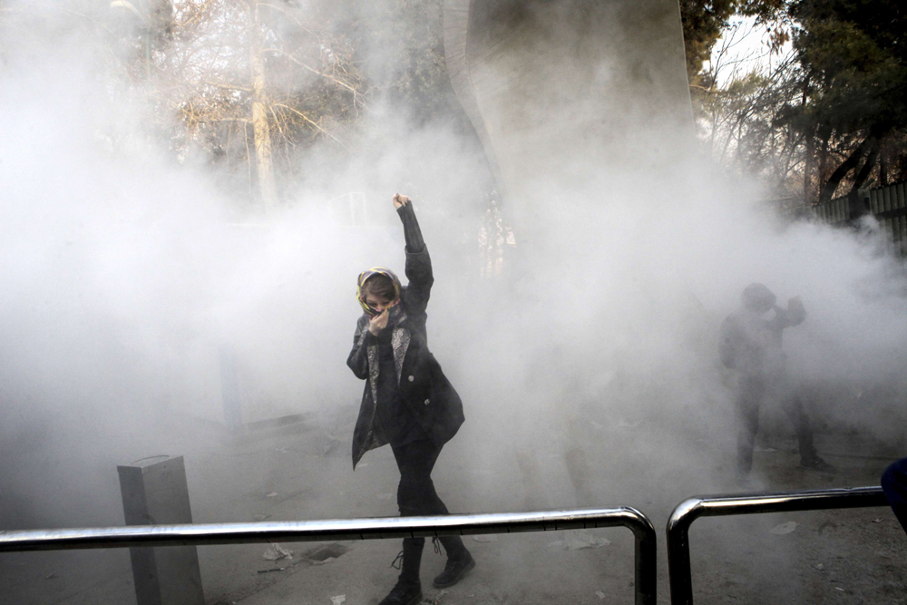 A file photo showing an Iranian university student attends a protest inside Tehran University while a smoke grenade is thrown by anti-riot Iranian police, in Tehran. (AP)