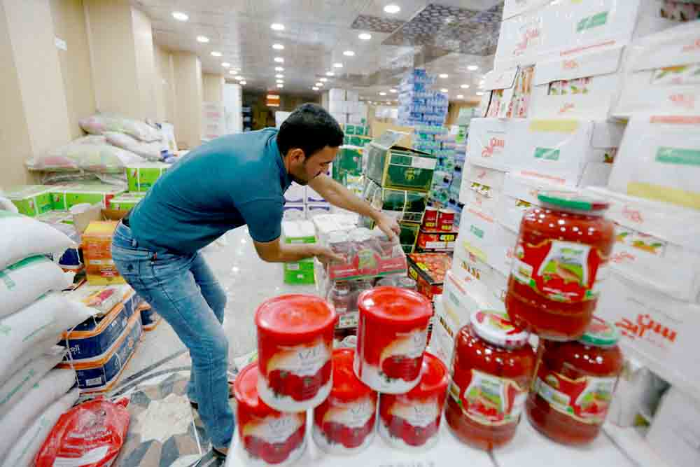 A shop worker arranges cans of Iranian tomato paste at a supermarket in the Iraqi city of Najaf, last October. (Reuters)