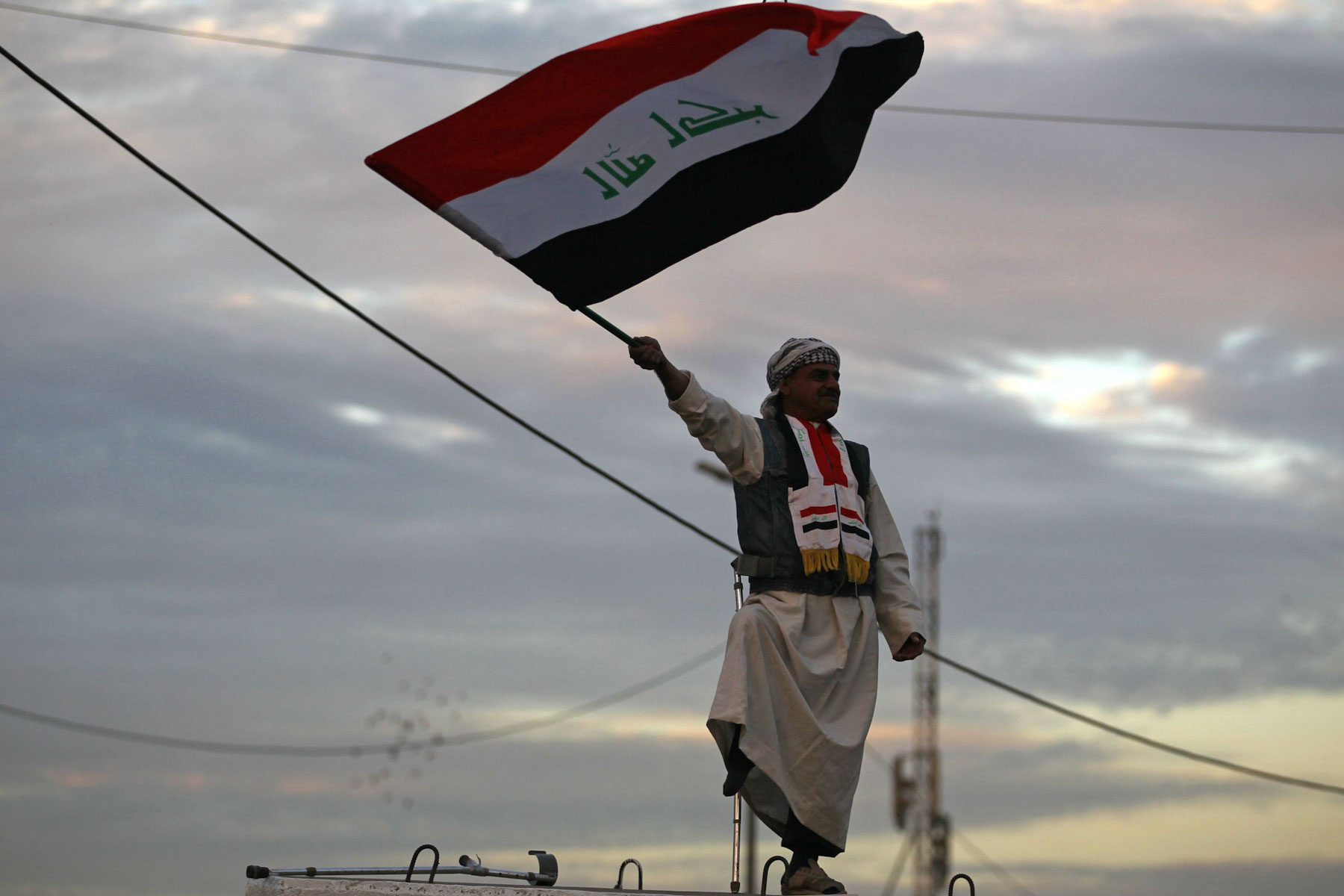 An Iraqi man waves the national flag in Baghdad's Tahrir Square during a gathering celebrating the end of the three-year war against ISIS. (AFP)