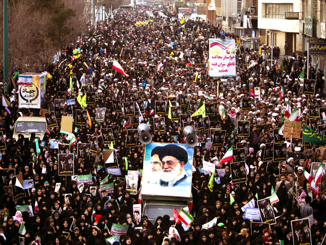 People march around a truck bearing a large poster with pictures of Iran's Supreme Leader Ayatollah Ali Khamenei (R) and late Leader Ayatollah Ruhollah Khomeini. (Reuters)