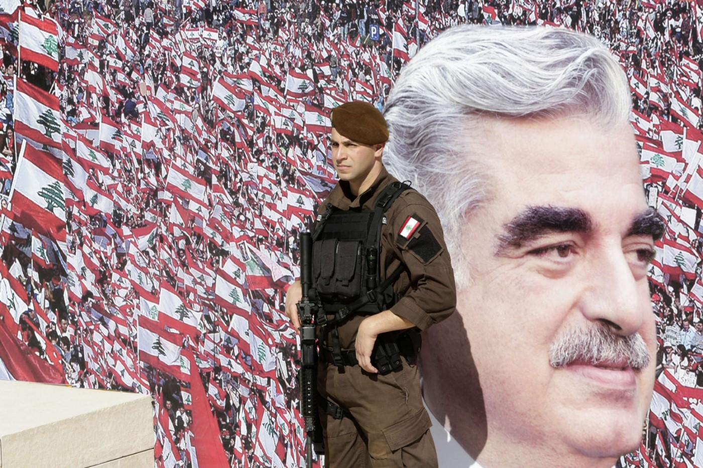 A member of the Lebanese security forces stands guard in front of a billboard bearing a portrait of slain former Lebanese Prime Minister Rafik Hariri in downtown Beirut. (AFP)