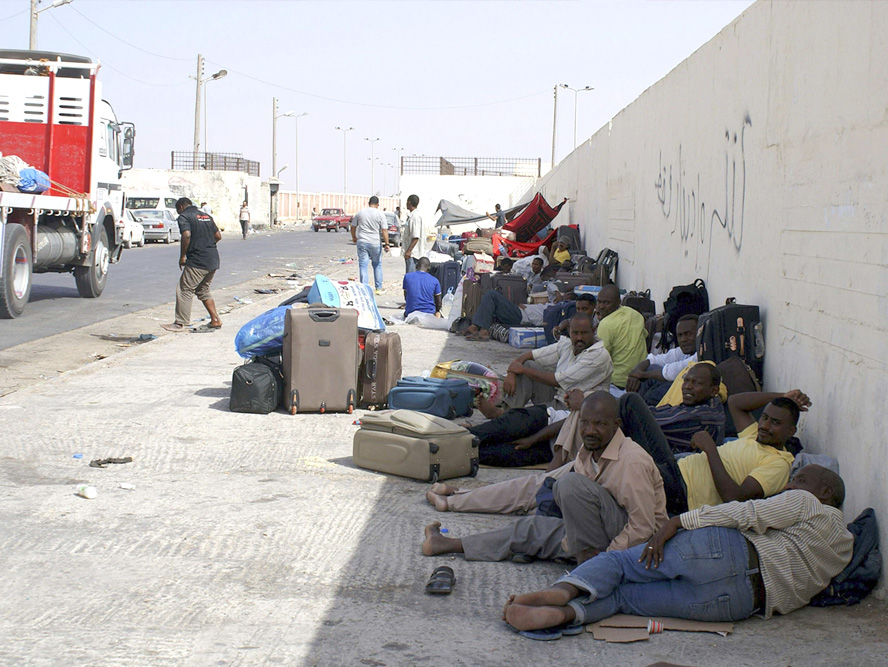 Another useless wall? Sudanese workers rest as they wait for Egyptian visas next to the Libyan-Egyptian border crossing in Musaid. (Reuters)