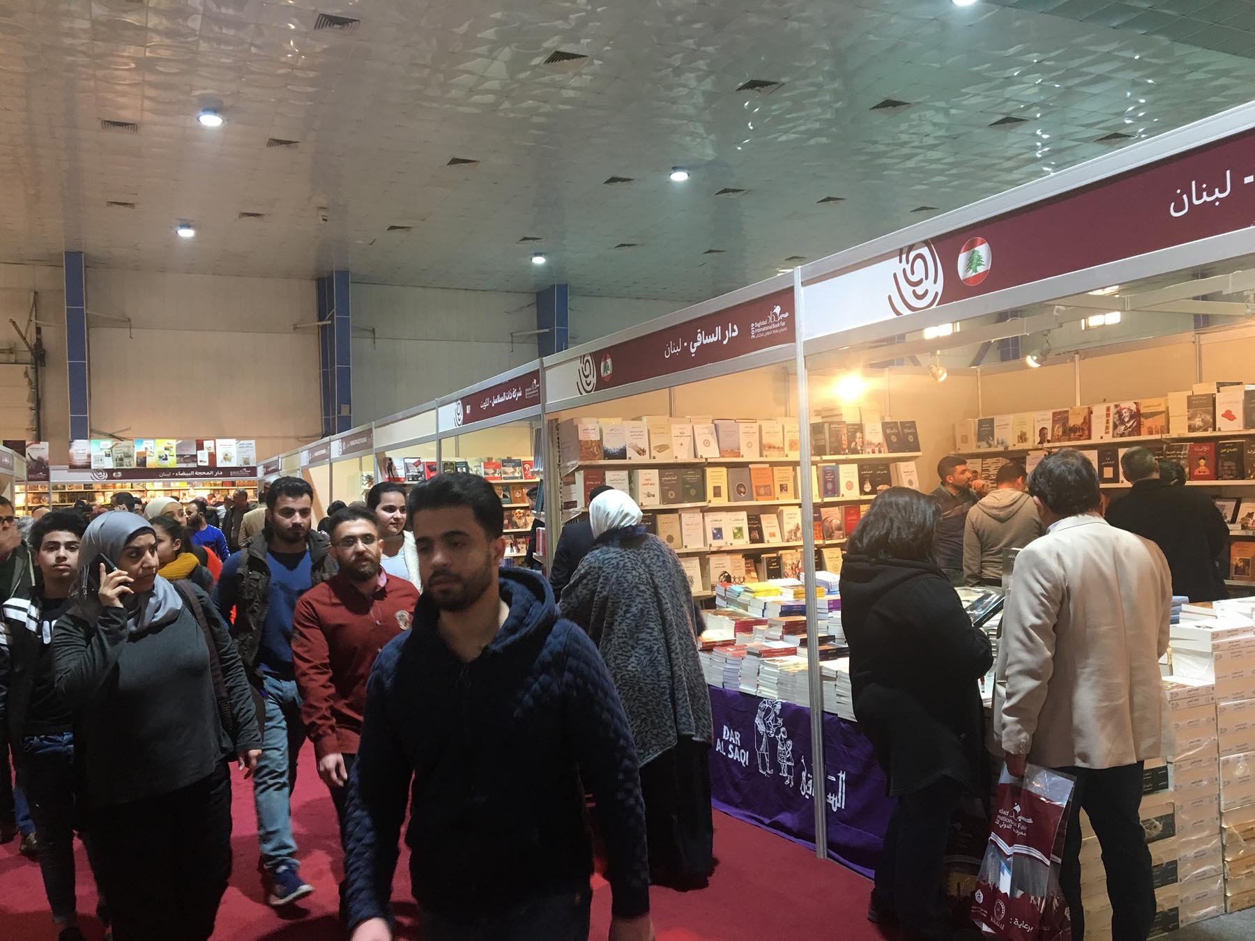 Visitors walk past the pavilion of Lebanon's Dar al Saqi publishing house at the Baghdad International Book Fair. (Oumayma Omar)