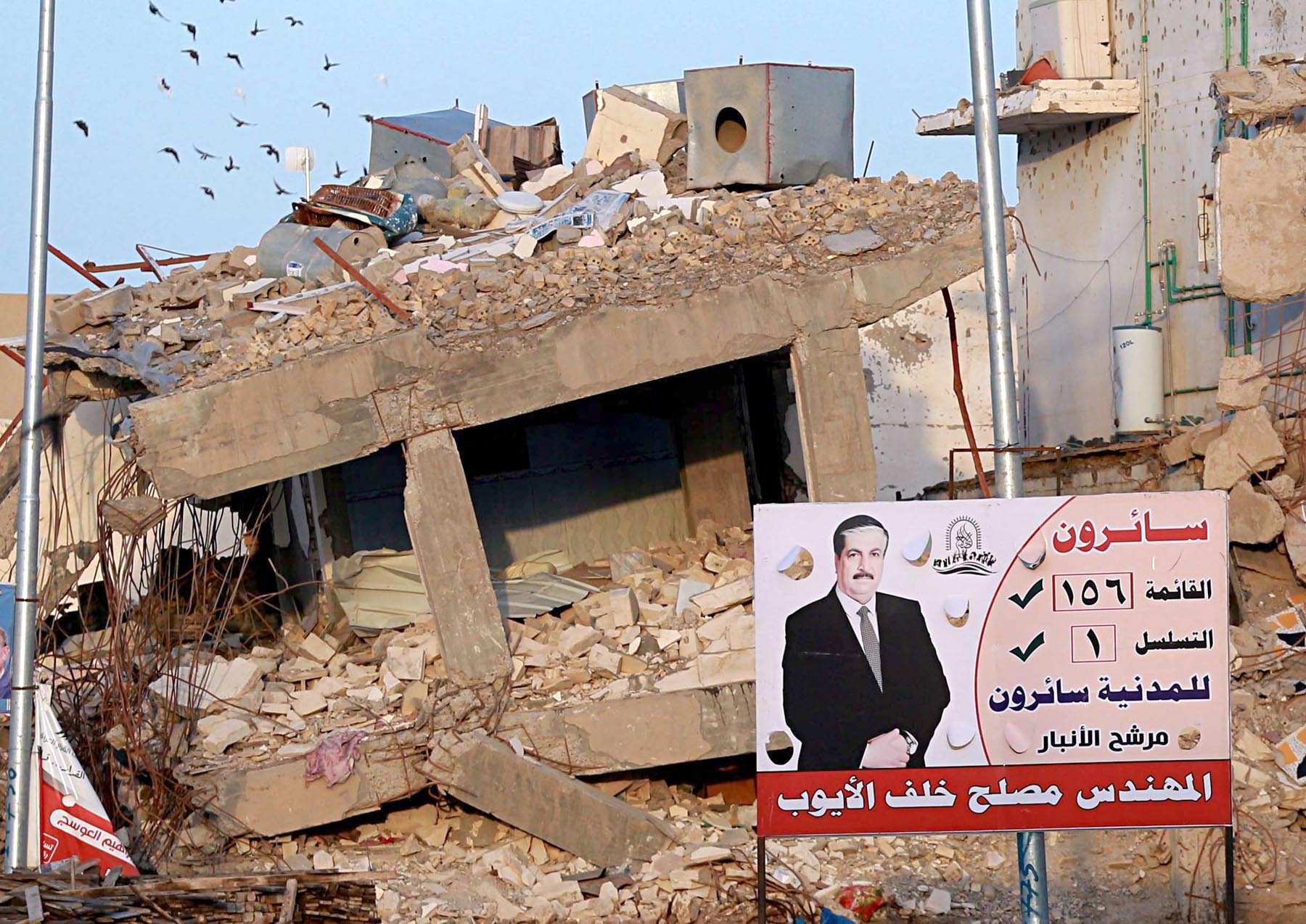 Political speak. A 2018 file picture shows campaign posters for parliamentary elections on display near destroyed buildings in Ramadi.   (AP)