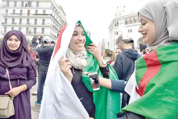 Key juncture. Algerian female protesters wear their national flags as they demonstrate against President Abdelaziz Bouteflika's bid for a fifth term in power, in Algiers, March 8. (AFP)
