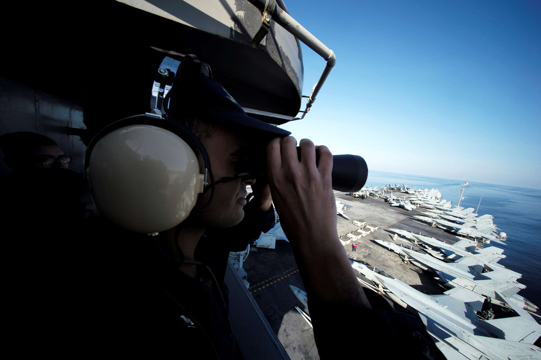 A US sailor keeps watch from the captain's bridge onboard the USS John C. Stennis as it makes its way to the Gulf through the Strait of Hormuz, last December. (Reuters)