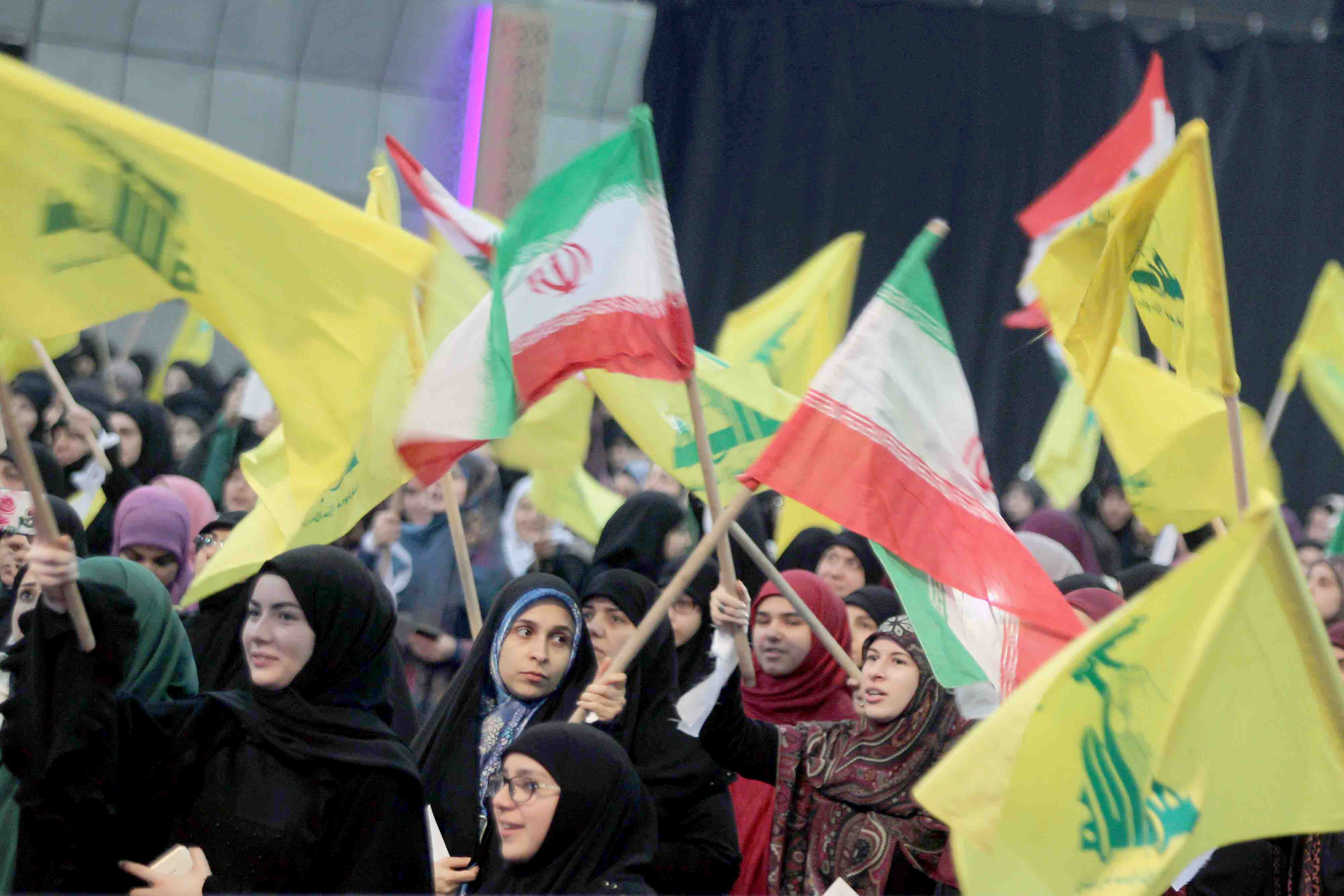 Hezbollah supporters wave flags of Iran and their Shia group during a rally to mark the anniversary of the Iranian Islamic Revolution, February 6. (DPA)