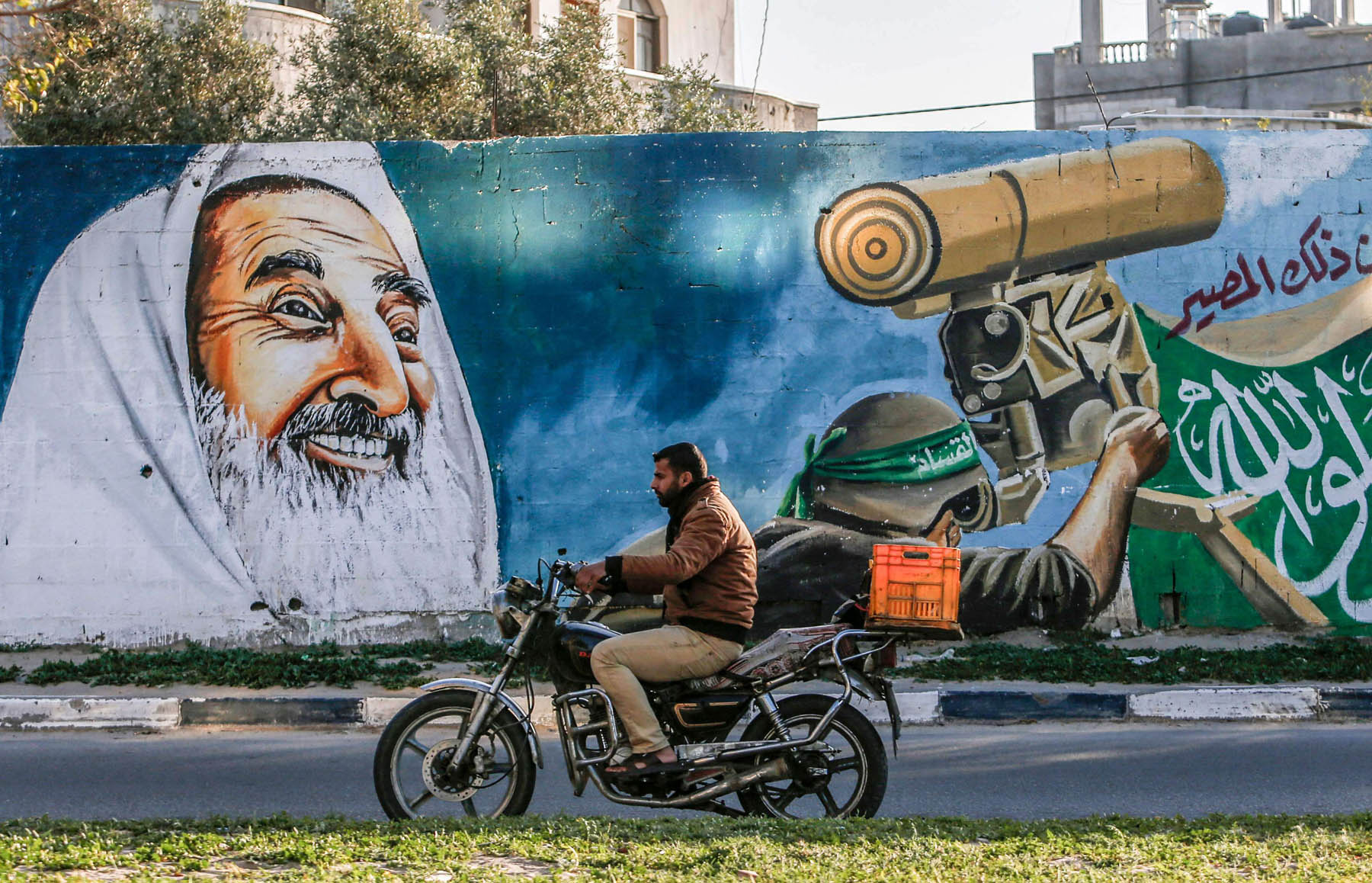 A Palestinian man drives a motorcycle past a mural depicting late Hamas spiritual leader Sheikh Ahmed Yassin and a masked fighter from the Qassam Brigades in Rafah in the southern Gaza Strip, March 14. (AFP)