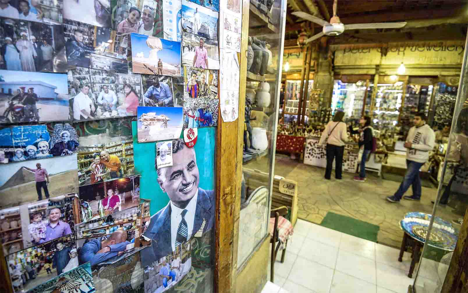 Tourist photos on display next to a poster of late Egyptian president Gamal Abdel Nasser (C) in a shop at a tourist bazaar in Luxor. (AFP)