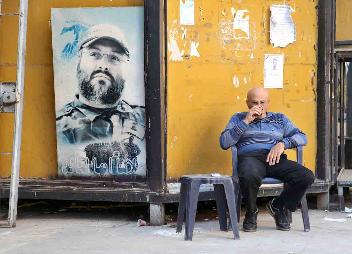 The ties that bind. A Lebanese man drinks coffee next to a poster of late Hezbollah military commander Imad Mughniyeh in the southern suburbs of Beirut. (AP)