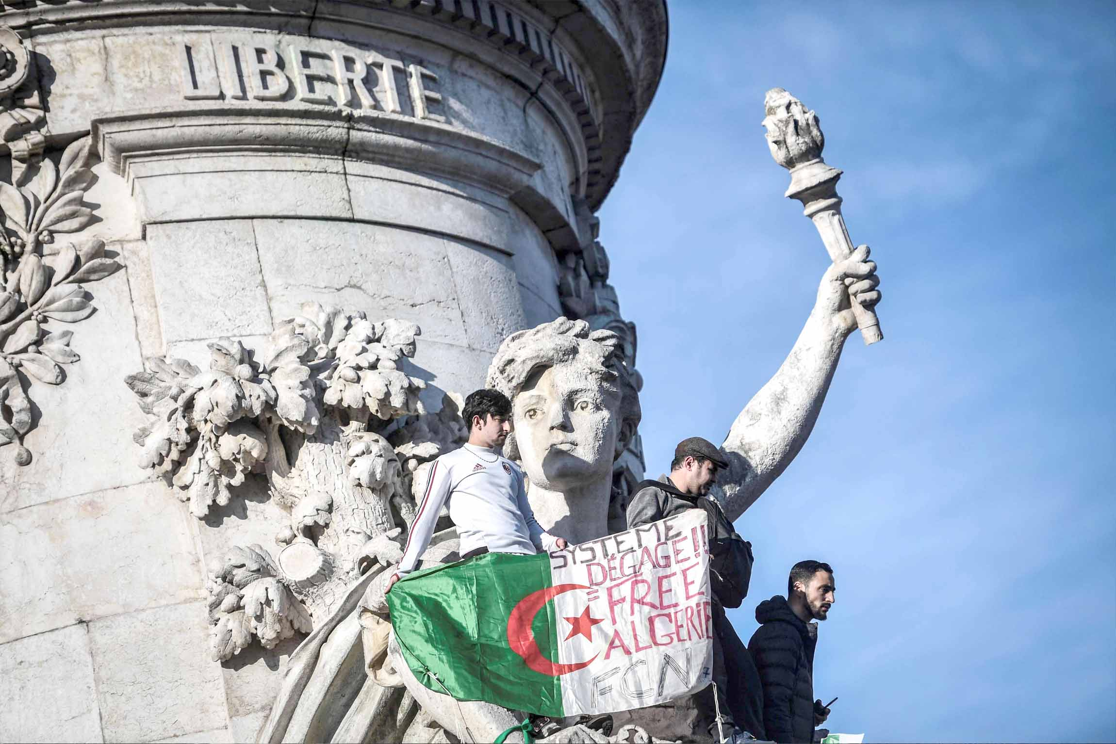 "The Algerian flag with the words written on it that read, ""System get out, free Algeria"" is held as protesters rally in Paris against the Algerian president's bid for a fifth term in office, February 24. (AFP)"