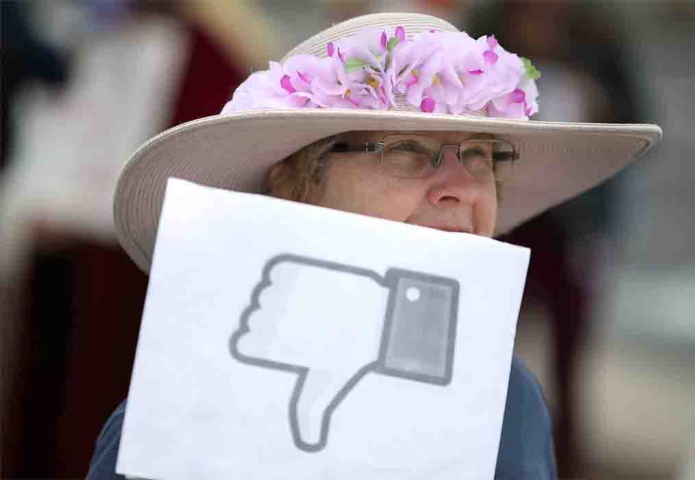 A woman holds a sign during a demonstration against Facebook in front of the company's headquarters in Menlo Park, California. (AFP)