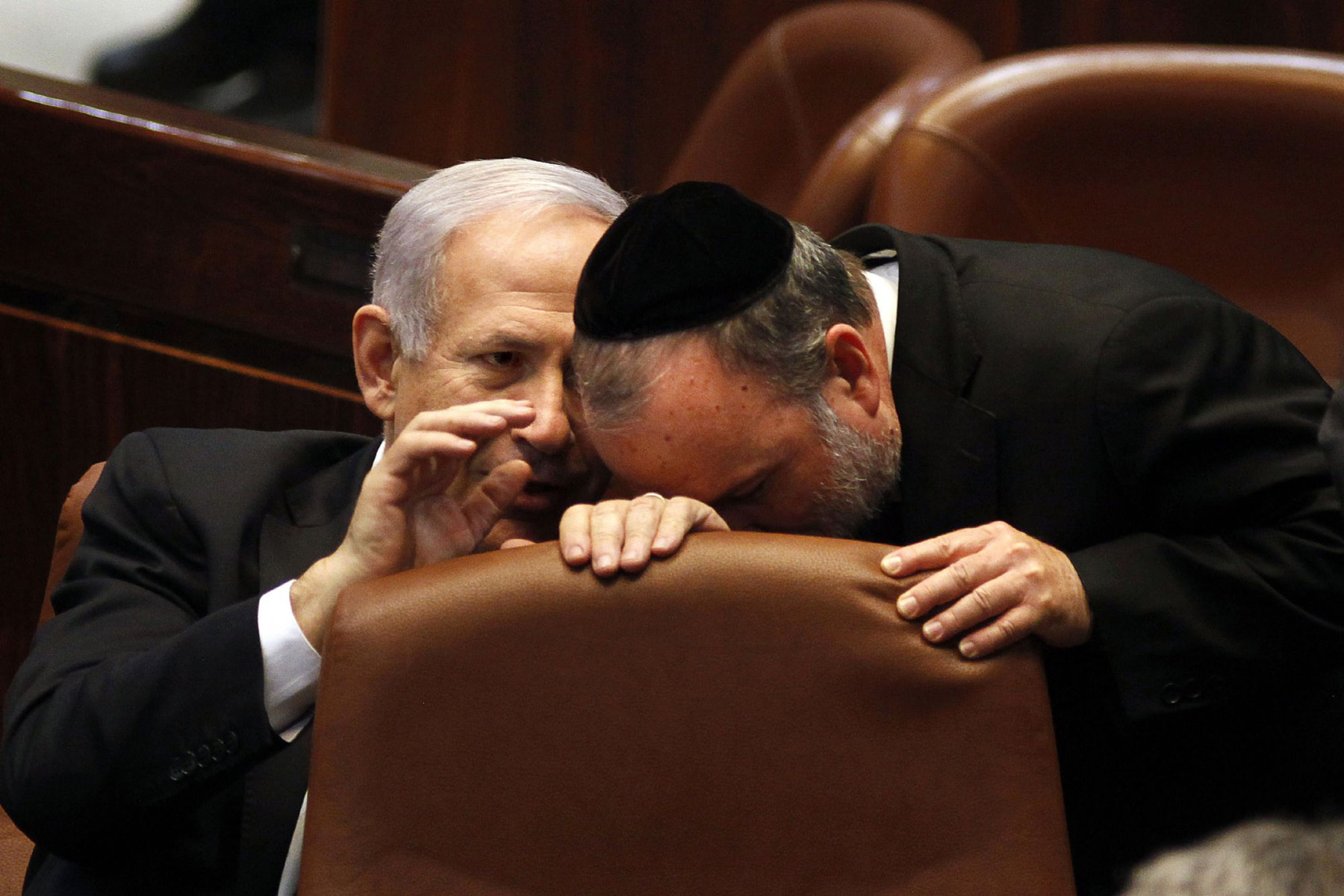 Israeli Prime Minister Binyamin Netanyahu (L) chats with an unidentified  ultra-Orthodox Member of the Knesset during a special session in Jerusalem. (AFP)