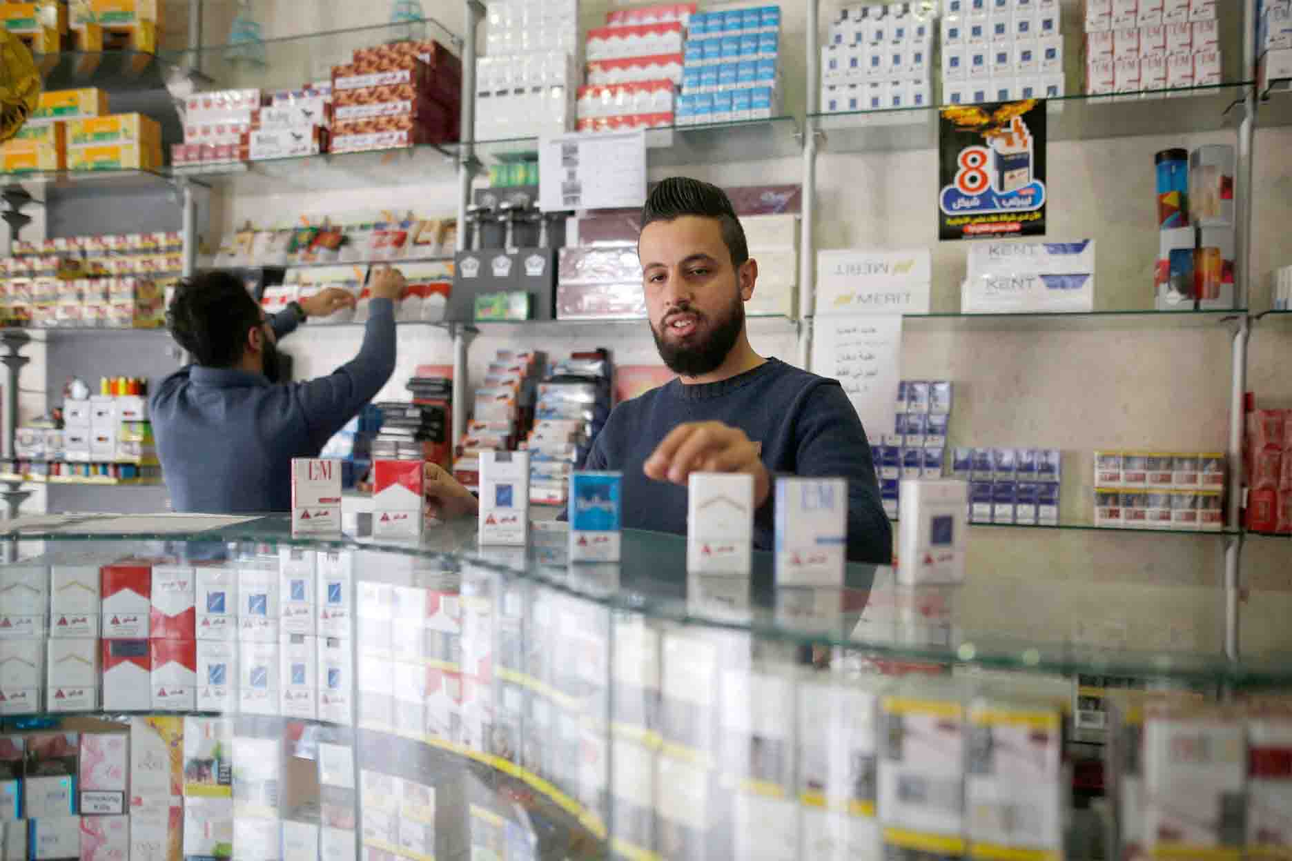Palestinian vendors sell cigarettes at a shop in Gaza City. (AFP)
