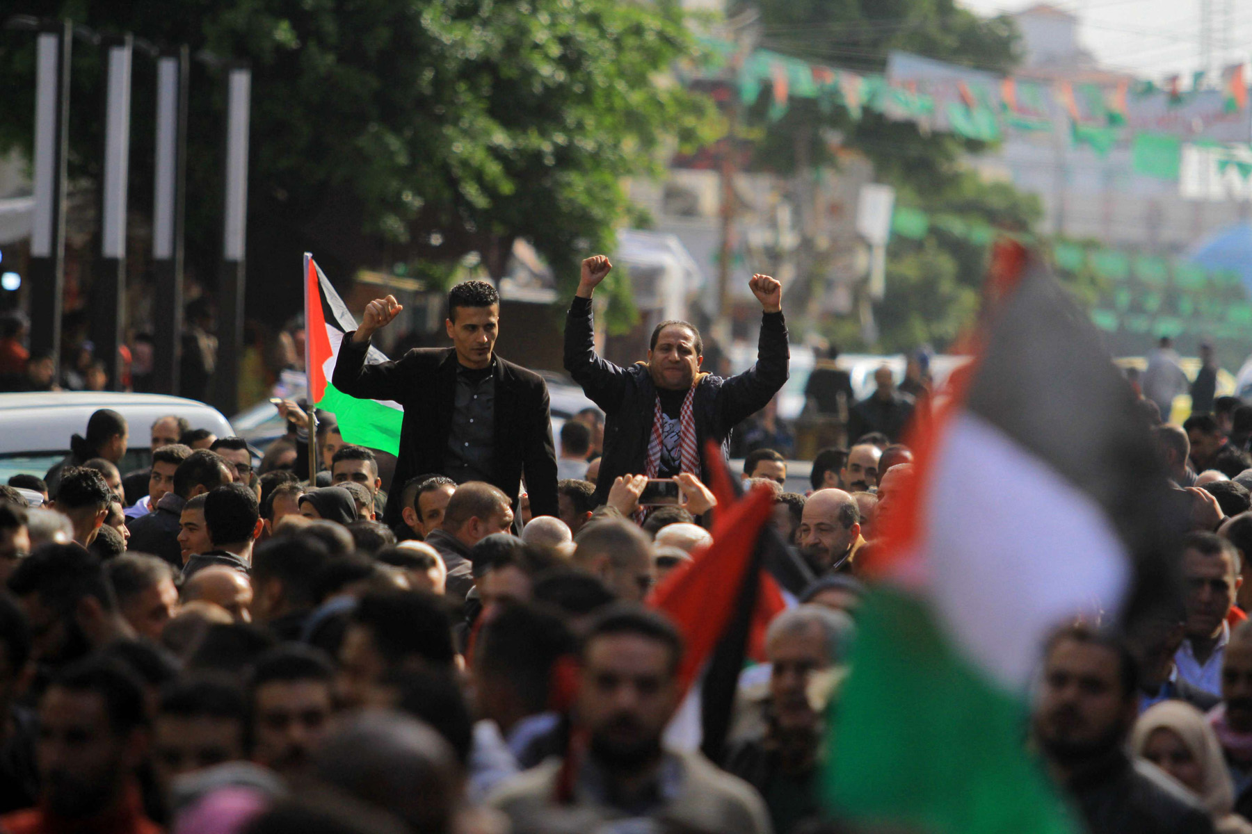 Palestinians take part in a protest in Gaza City to support reconciliation efforts between Fatah and Hamas, January 12. 			     (dpa)