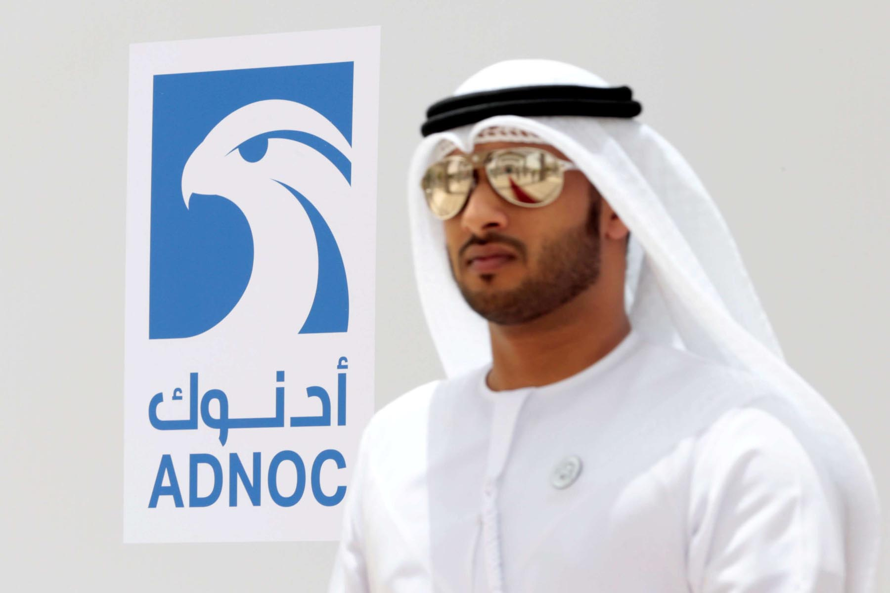 An Emirati man walks by the logo of ADNOC in Ruwais.  (Reuters)