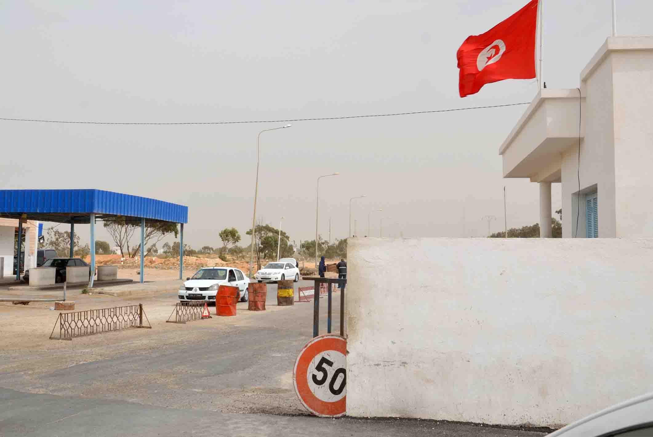 Vehicles wait near the Tunisian customs post at the Ras Jedir border crossing with Libya, south of of Ben Guerdane. (AFP)