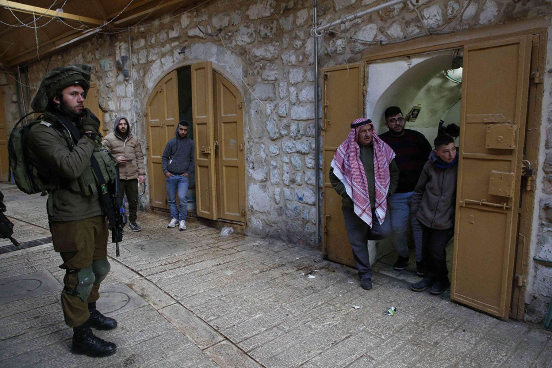 An Israeli soldier stands guard as Palestinians watch Jewish settlers (unseen) touring the Palestinian side of the old city market in Hebron, last February. (AFP)