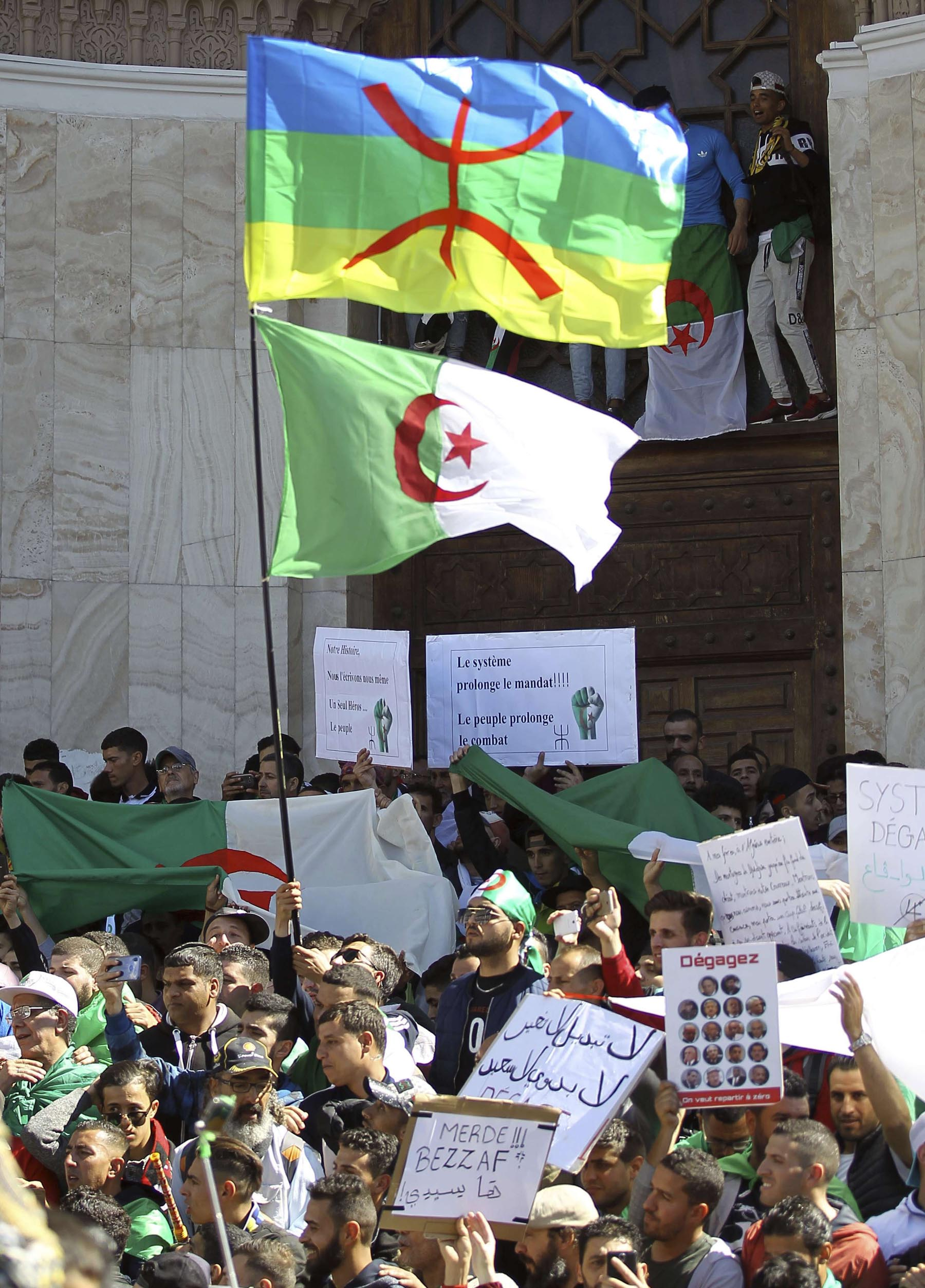 Identity issue. During a protest in Algiers, March 15, the Algerian flag is hoisted below the Berber banner.                  (AP)