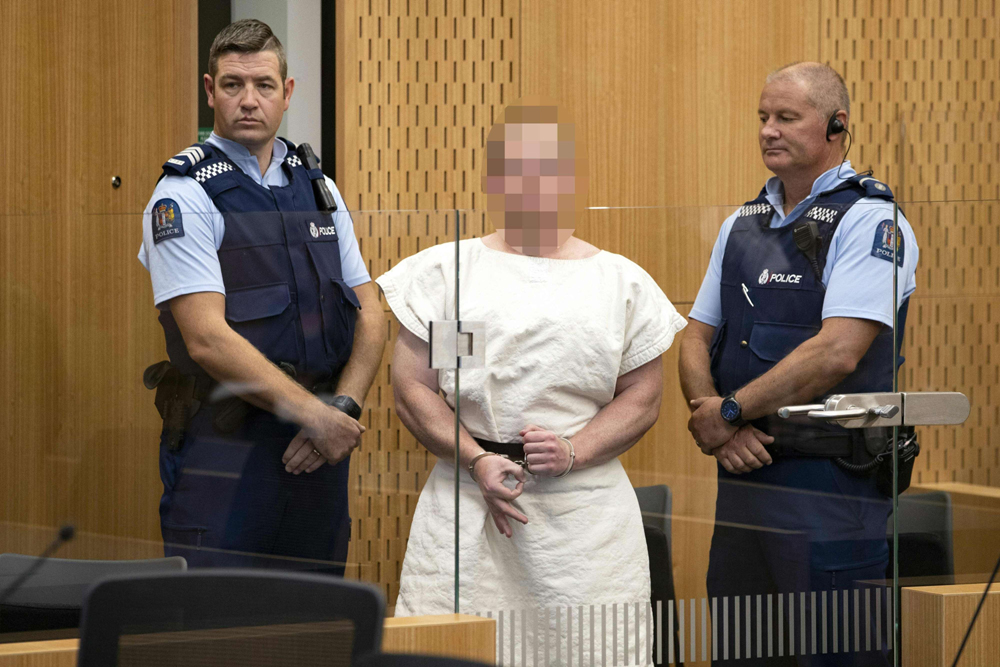 Brenton Tarrant, the man charged in relation to the mosque massacre, makes a sign to the camera during his appearance in the Christchurch District Court, New Zealand, on March 16. (AFP)