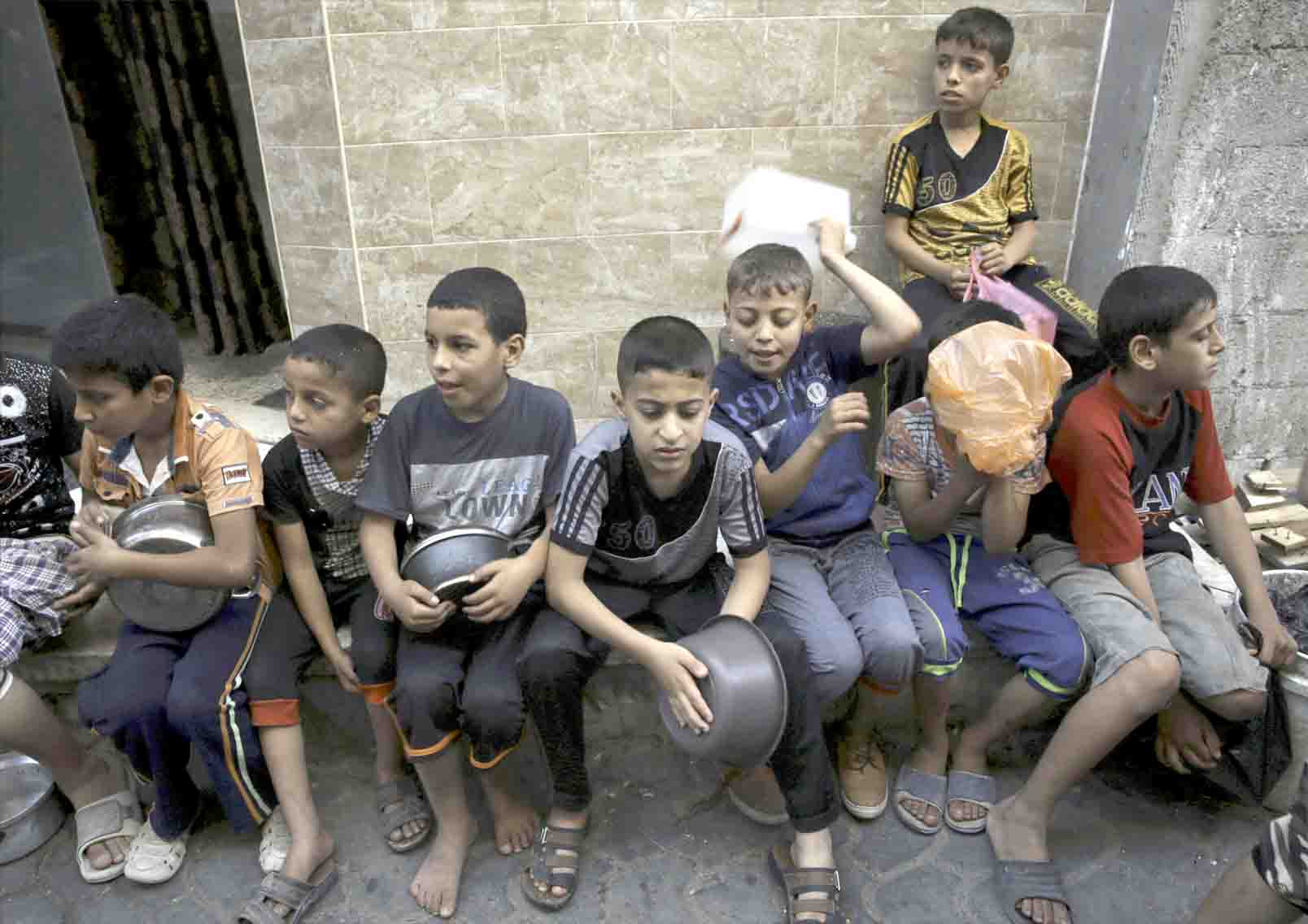 Indignity. Palestinian children wait to receive free meals in Gaza City. (AP)